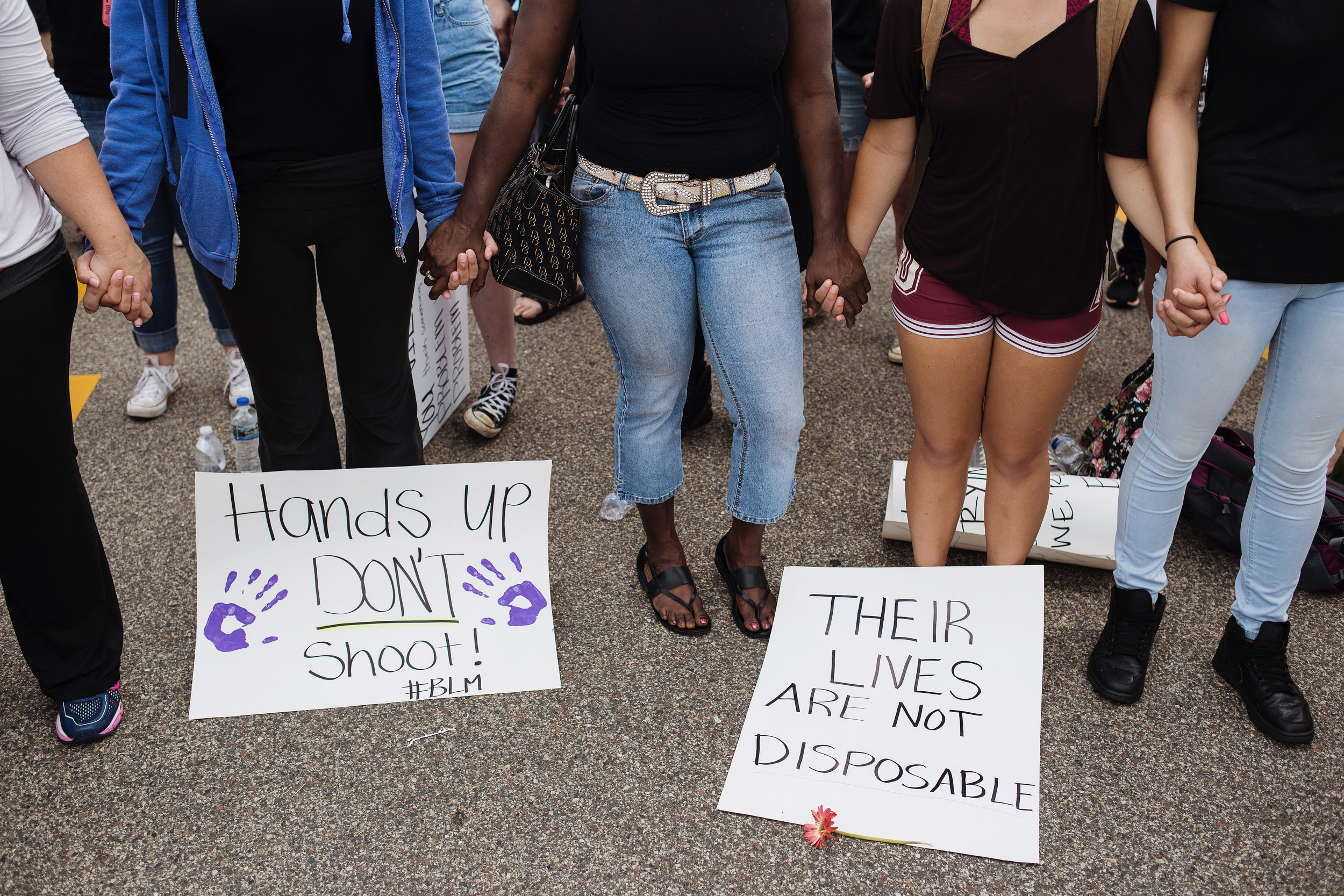 Protestors held hands during a group prayer outside of the St. Anthony Police Department, where they rallied demanding justice for Philando Castile on Sunday, July 10, 2016.