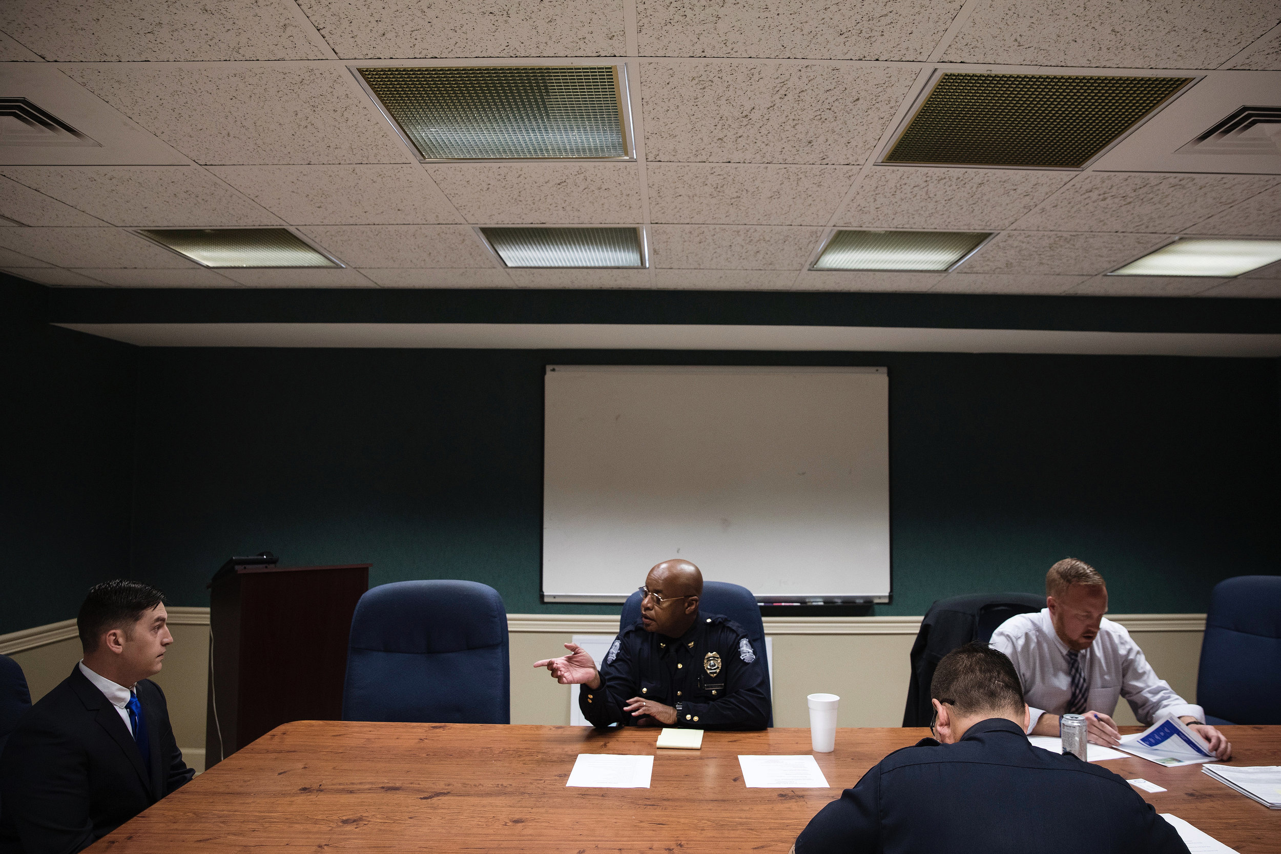 """Wayne makes introductions before the start of an interview for a police officer. The department was seeking to fill three open positions to restore a full staff of 24. He sees hiring new officers as an opportunity to achieve his vision for diversity in the department. People have asked Wayne why the police department doesn't hire people of color, leaving him frustrated. """"I still want the best person for the job. I would love to see people of color and more females apply, but if they don't apply then they're not a part of the interview process. It's that simple."""""""