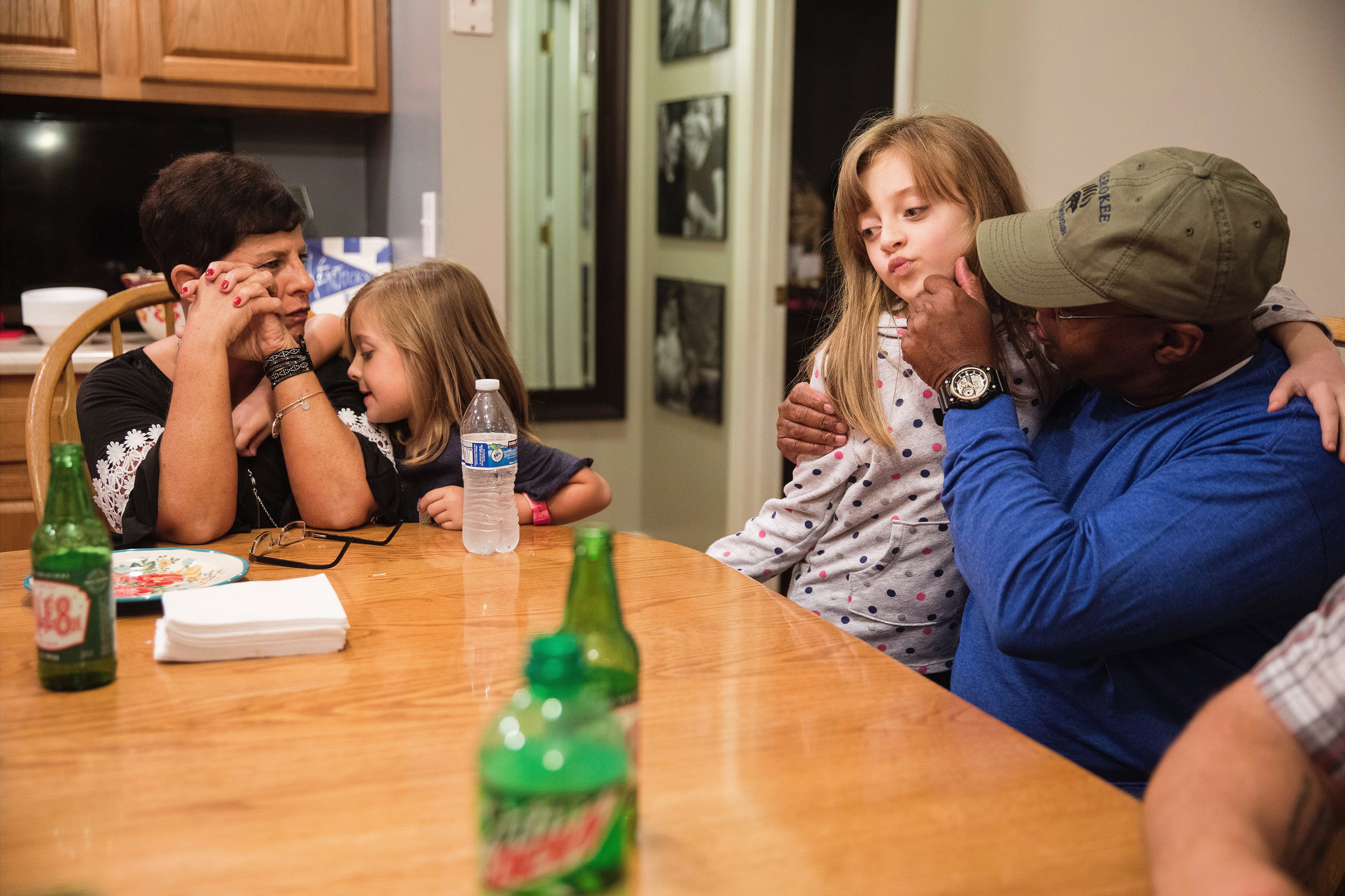 """Wayne embraces his granddaughter, Makynleigh, 7, as Anniston, 5, clings to Christy at dinner. For Wayne, his four granddaughters are his world, and he and Christy care for them after school most days during the week. After a long day of work at the police department, Wayne will typically color or watch SpongeBob SquarePants with his granddaughters, allowing him to decompress. """"I can feel the stress leave my body because of their innocence,"""" he says."""