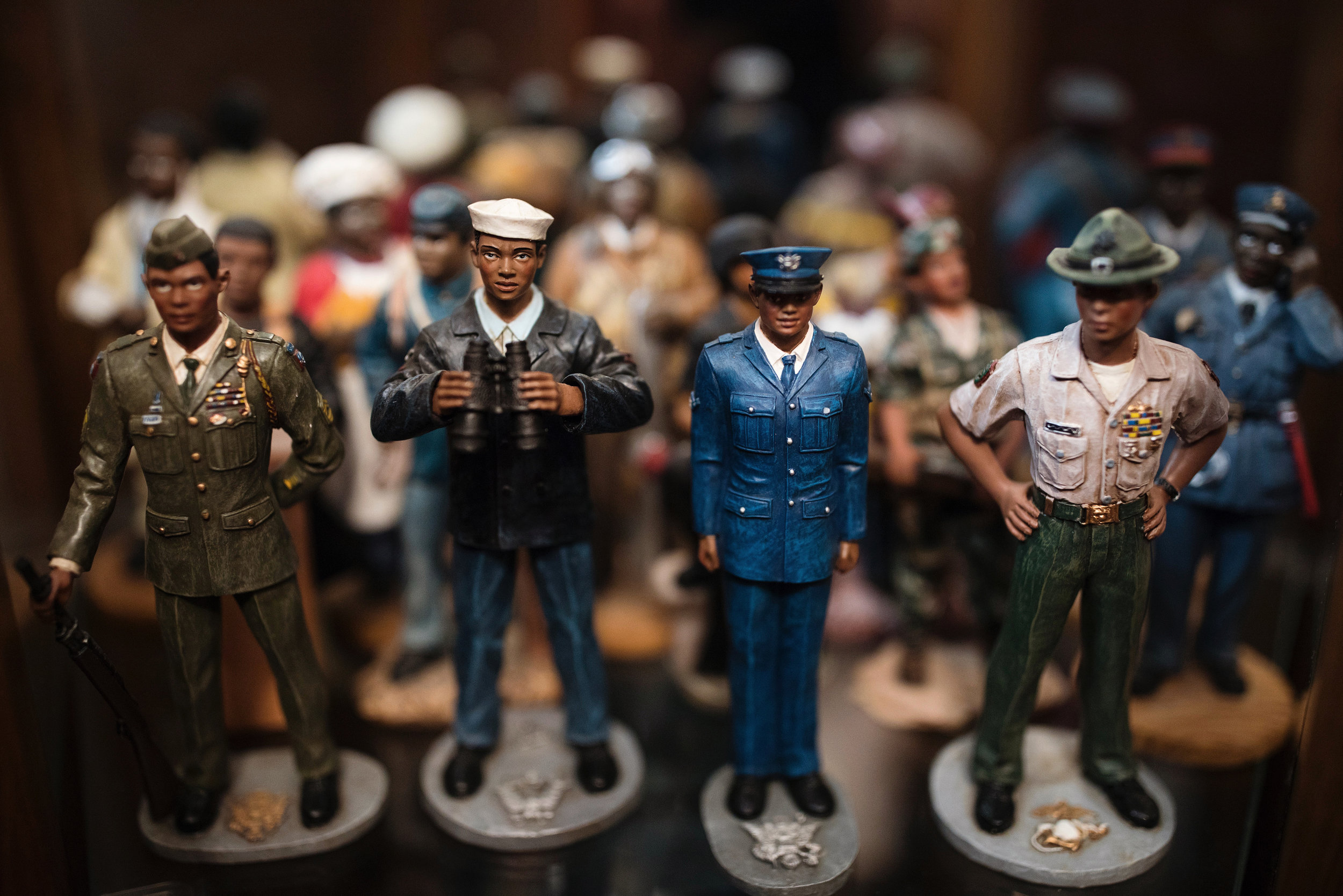 """Figurines representing African-Americans in various professions sit on a shelf in Wayne's home office. Wayne hopes to inspire young people of color in the same way these figurines inspire him. His message to young people: """"You don't have to be law enforcement like me, but you can be a professional. It may be harder, but you can do it; you've just got to want to do it."""""""