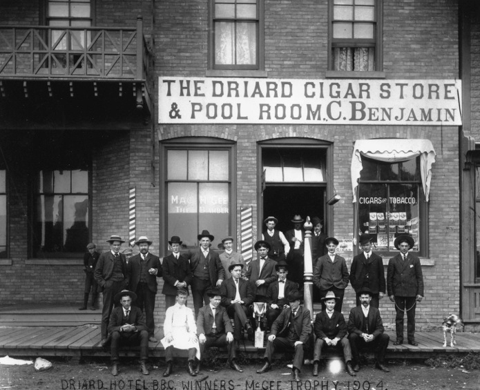Previous to the men's wear store Chas Benjamin owned a small cigar shop inside the Driad Hotel in Wetaskawin, Alberta. He is the well dressed fellow on the right with the dog on the leash. Not only could he sport a cowboy hat, but he was pretty dapper as well.