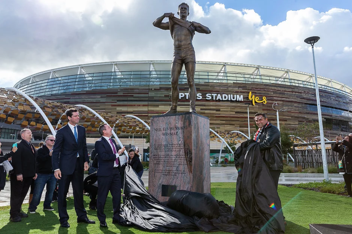 The statue is unveiled by CEO of the AFL Gillon McLachlan, the Premier of Western Australia Mark McGowan, and the great man himself.