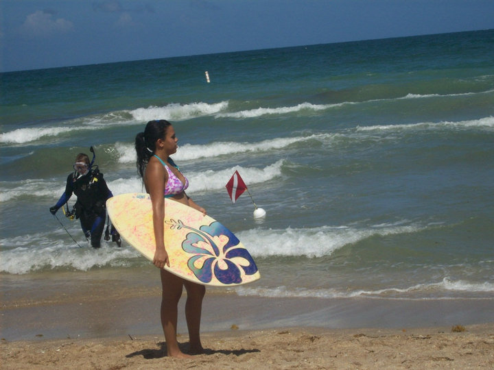 Photo of the author holding a skim board at Lauderdale by the Sea while a scuba diver comes out of the waves. Ancestral land of the Seminole tribe.