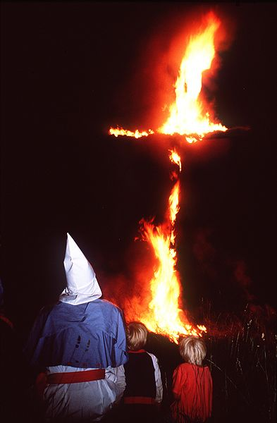 In this photo shot October 1987 in Oak Hill, in Jackson County, Ohio, Klansmen Joe Gosiniak watches a cross burn along with his children. The cross burning was held on the private land of farmer William Donta.  Photo courtesy of Paul M. Walsh (WikiCommons)