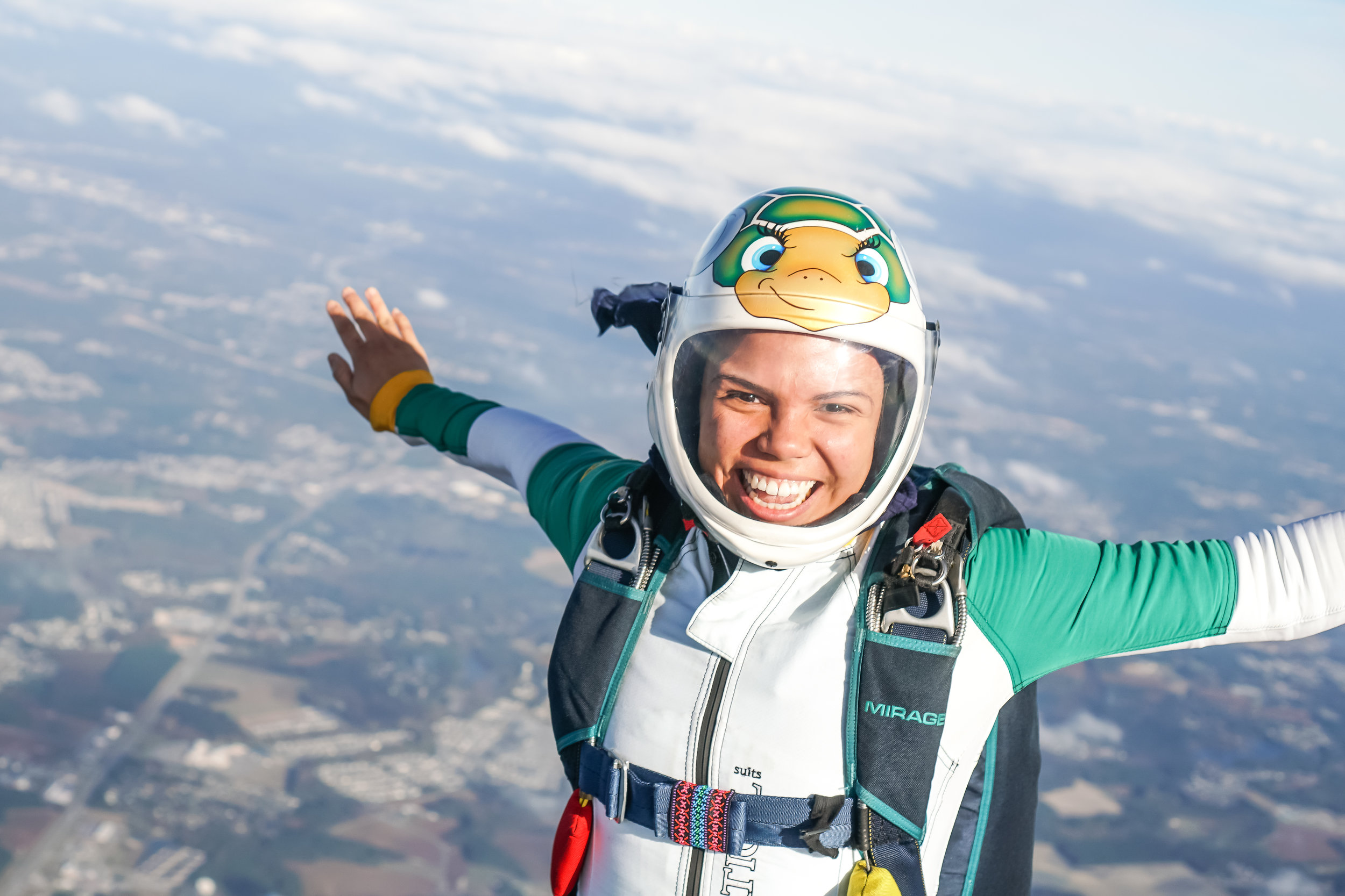 Covering her hair with a buff underneath her skydiving helmet helps protect her curls from 120mph winds.  Photo courtesy of Elliot Byrd