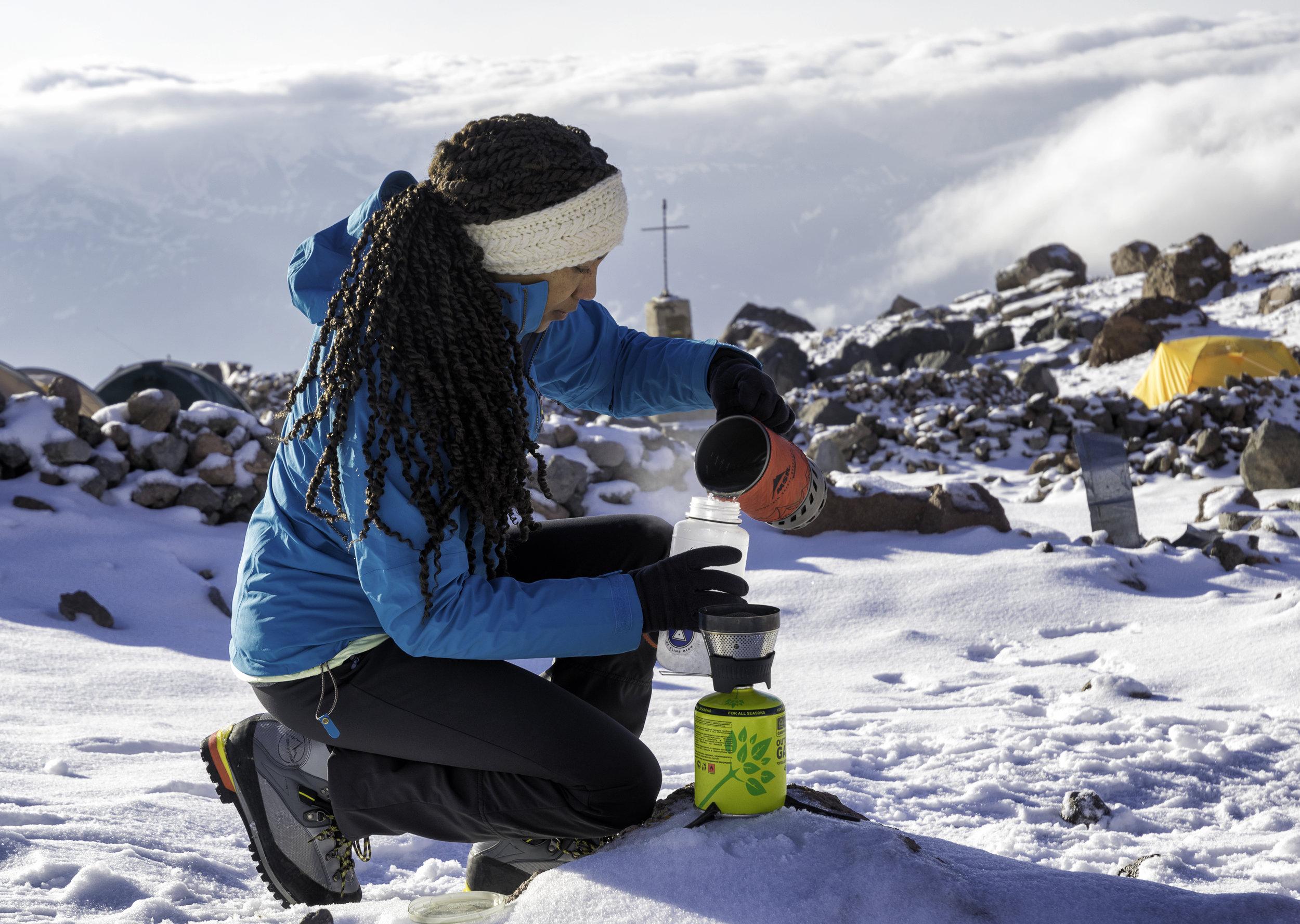 Rebecca Ross prepares a meal on Mt. Kazbek high up in the Georgian Caucuses.  Photo courtesy of Alper Gunay