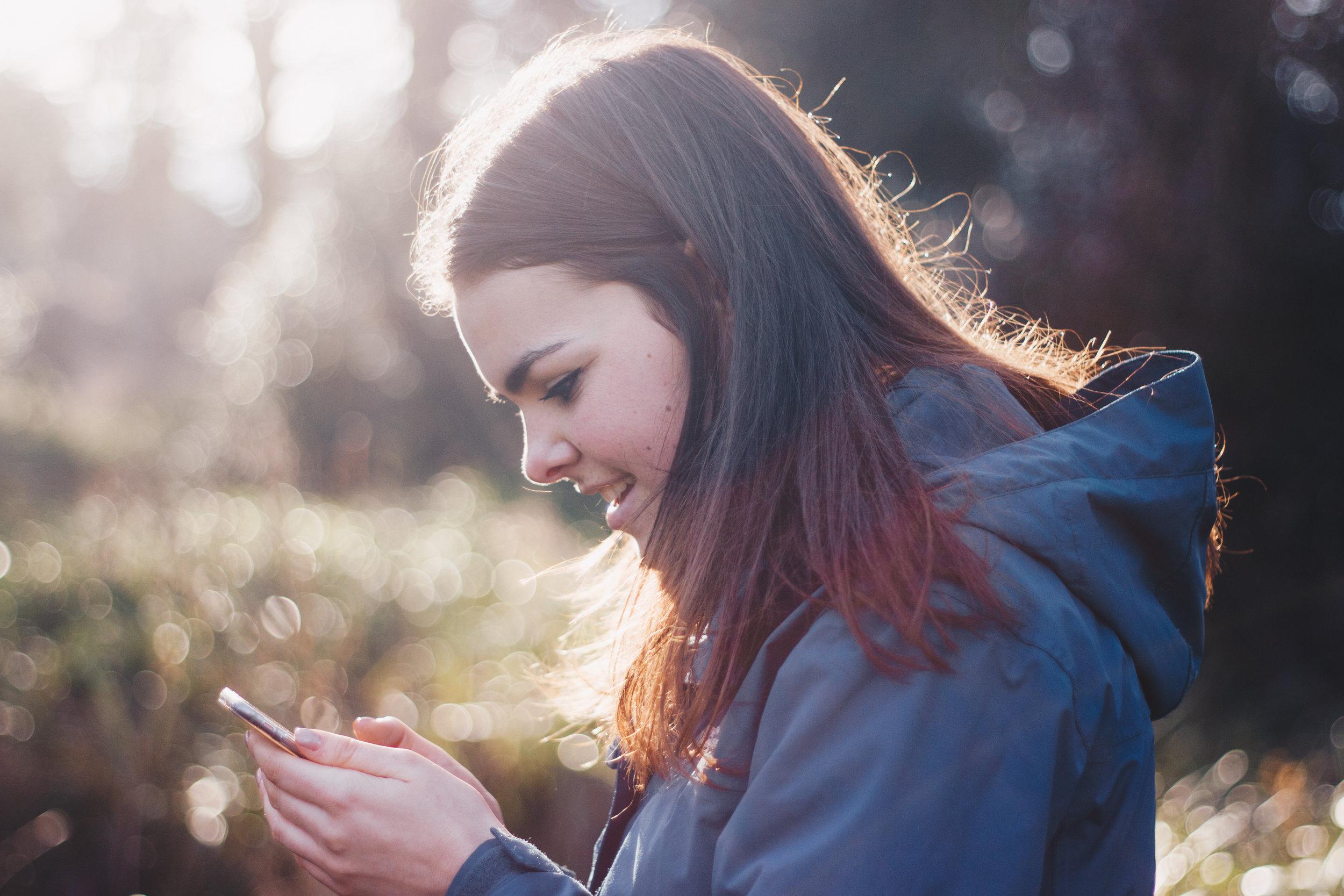 Woman looking down at smartphone,  Luke Porter  (CC0)