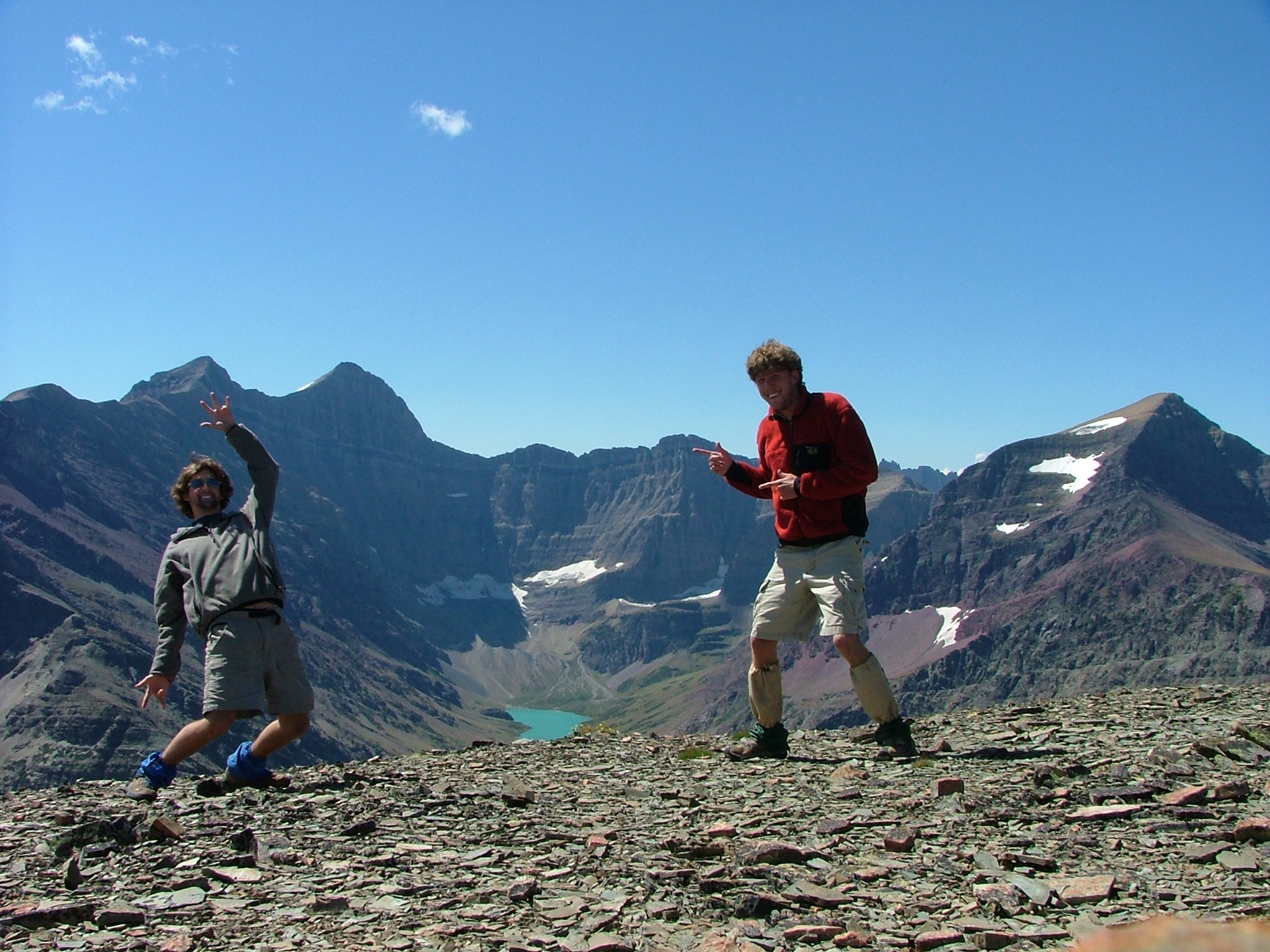 """A pair of callow young mountaineers encourage you to """"Rock On"""" while following the long, long ridge from Mt. Wynn to Mt. Siyeh in the distance. Cracker Lake peaks up at the base of Siyeh in the middle of the photo."""