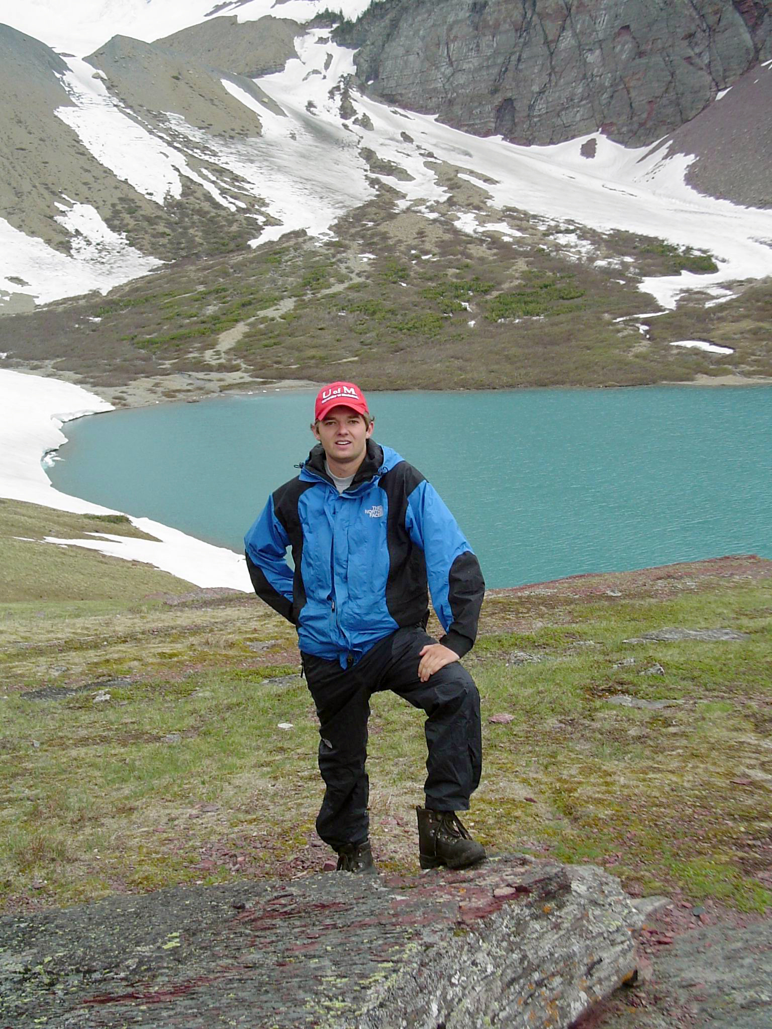 A stalwart hiker poses at Cracker Lake, very near the location of the Cracker Jack Mine. Photo Credit to Howard Stone.