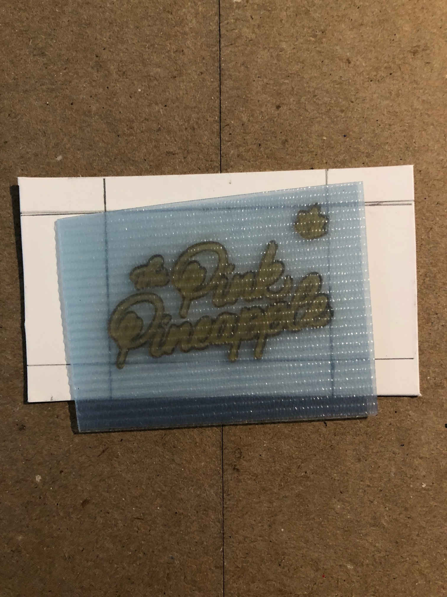This is a snap shot of a polymer plate being registered to the card. ALL DIGITAL DESIGNS are made into polymer plates. We then put this plate on the press and print from it. It's tedious and why it has to be done one layer at a time. This polymer plate is for only the black printed area on the front of the card. There is a separate plate for the pineapple itself  and  the back of the card. Since I press one card at a time, and they purchased 1,000 cards. Each card was pressed 3 times (twice on the front, and once on the back). That makes it 3,000 presses total PLUS the extra four color cards I made and 500 two color coasters. So, at least 4,500 presses in the week.