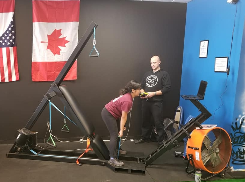 Woman pulling on cables on exercise equipment with innovate health and performance personal trainer