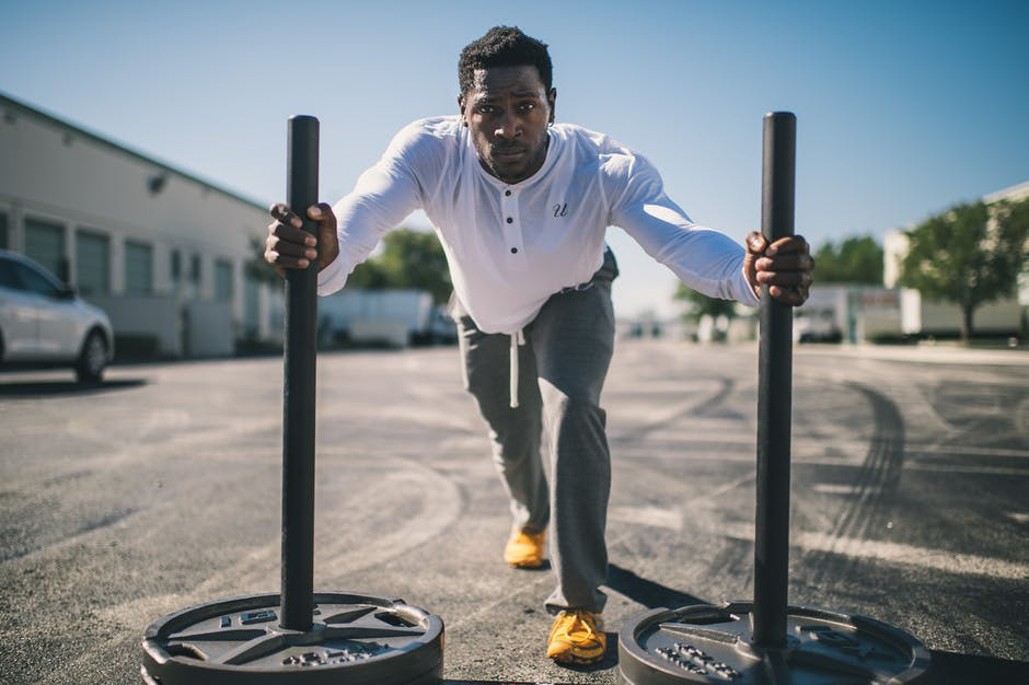 Man pushing two poles with large weights during workout