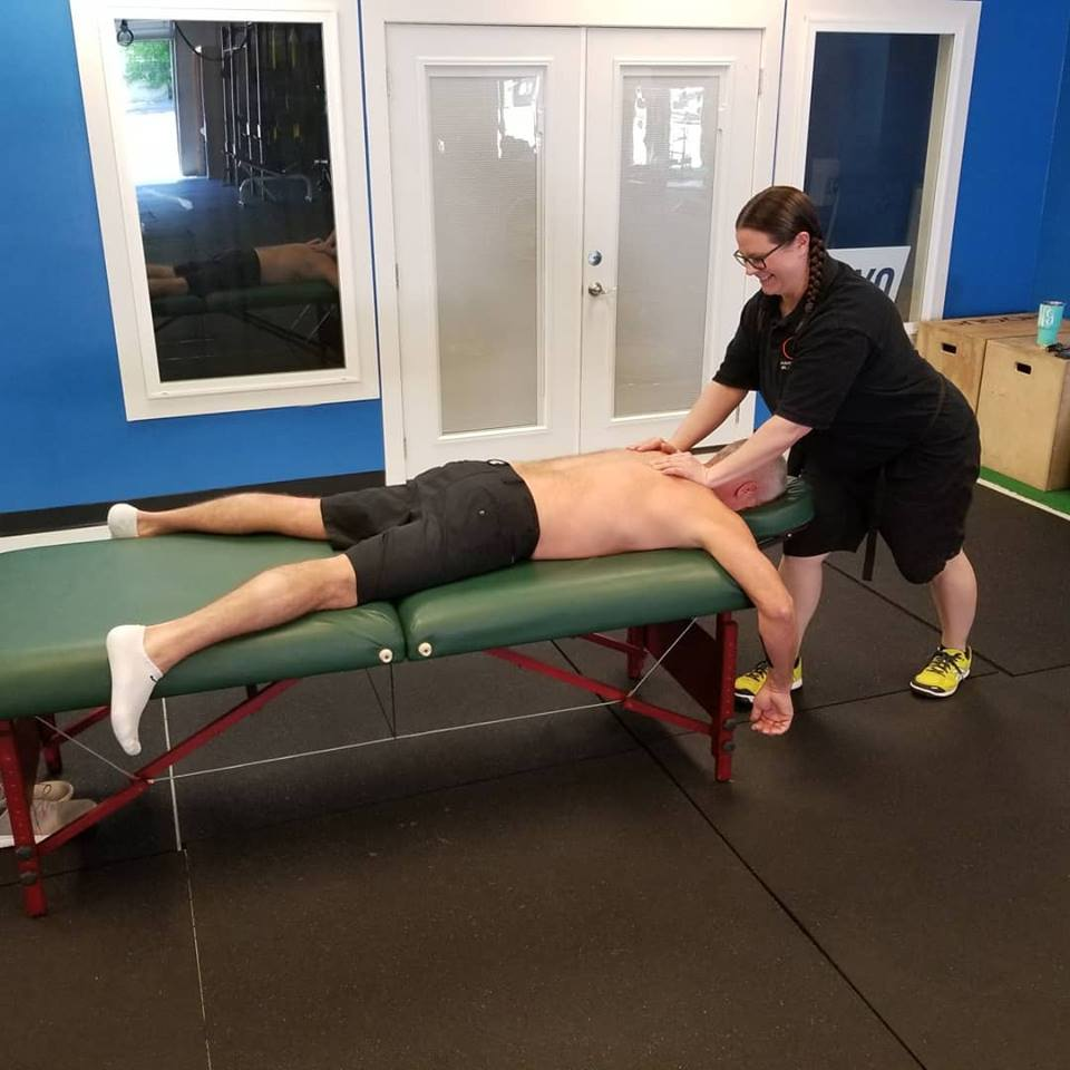 Man laying on table getting massage from Innovative Health and Performance massage therapist
