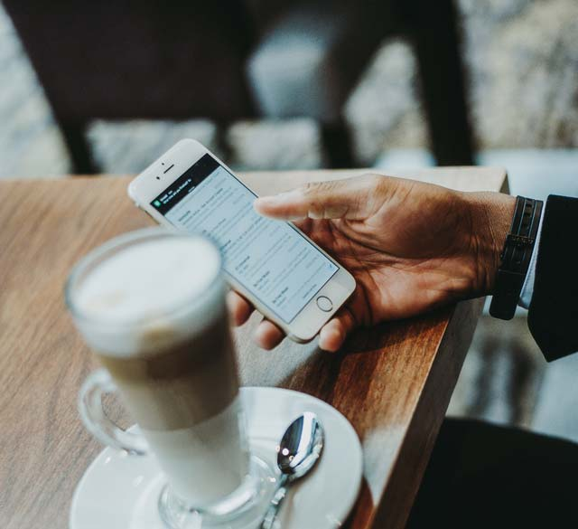 hand-holding-a-phone-looking-at-an-email-at-a-coffee-table.jpg