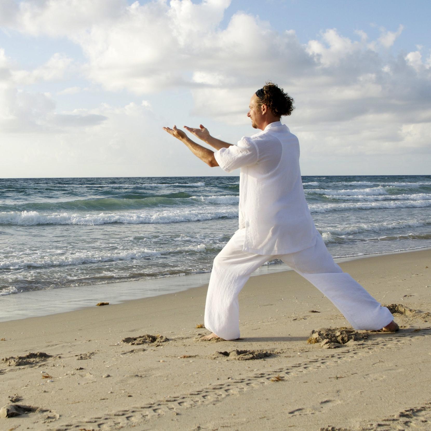 man-dressed-in-white-praticing-tai-chi-on-beasch.jpg