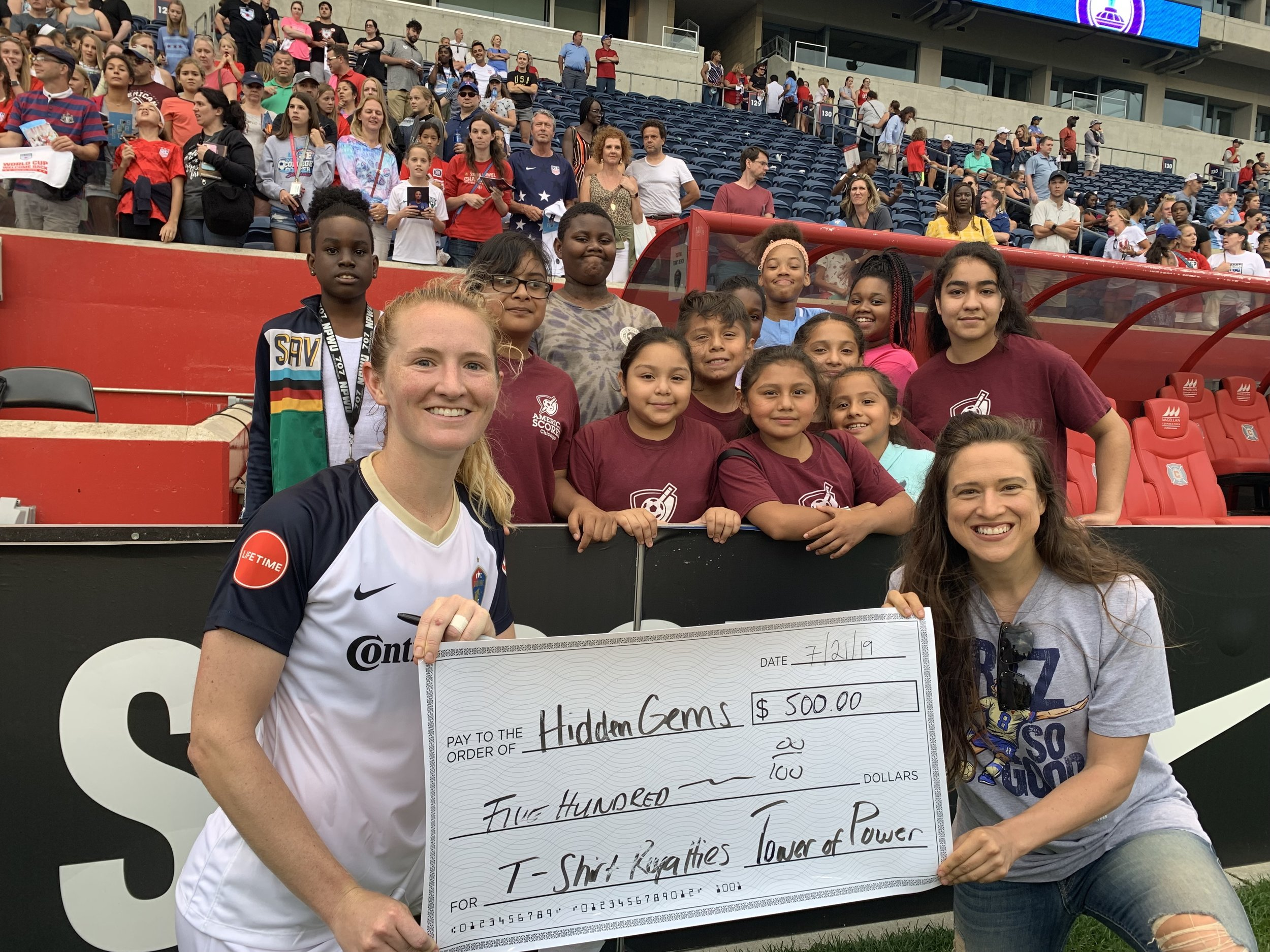 World Cup Champion Sam Mewis presents a check for her $500 donation