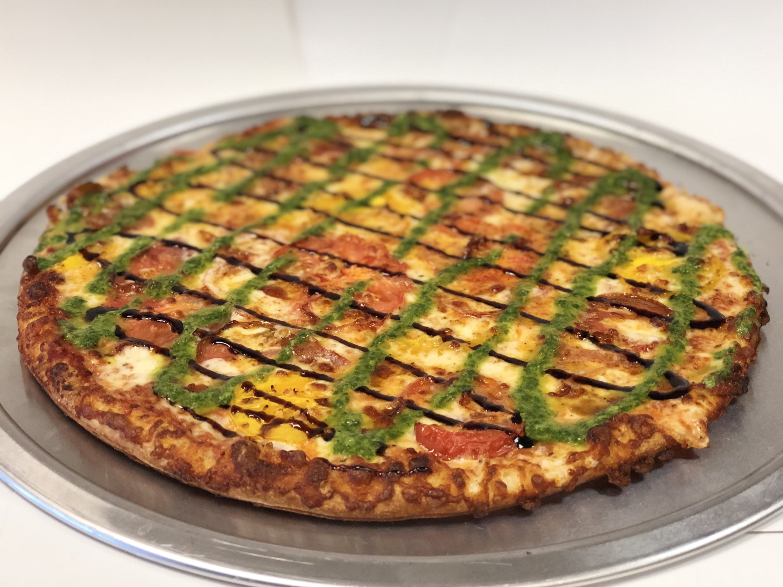 Piper's Margherita Pizza!  This tasty Thin Crust pizza starts with our  house-made marinara sauce, garlic, and  mozzarella cheese. Then it's topped with fresh sliced heirloom tomatoes and a drizzle of  balsamic glaze and basil pesto.  Small  Medium  Large  X-Large $15.99  $19.46  $22.69  $25.25