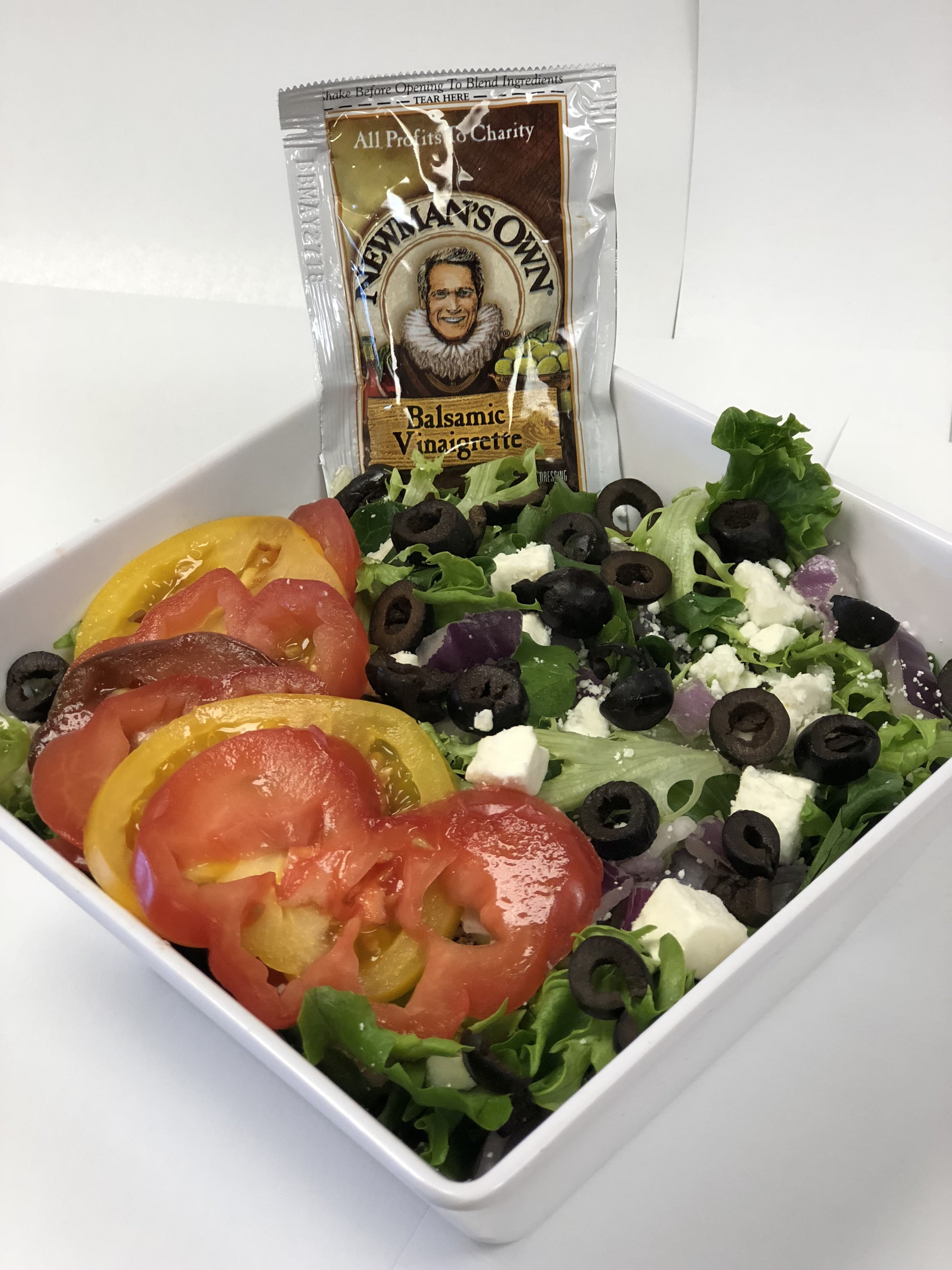 Heirloom Tomato Salad  Starting with a bed of Arcadian Harvest Emerald lettuce and topped with red onions, Feta cheese, sliced heirloom tomatoes, black olives and served with Balsamic dressing on the side.  Small: 6.84      Large: 8.73