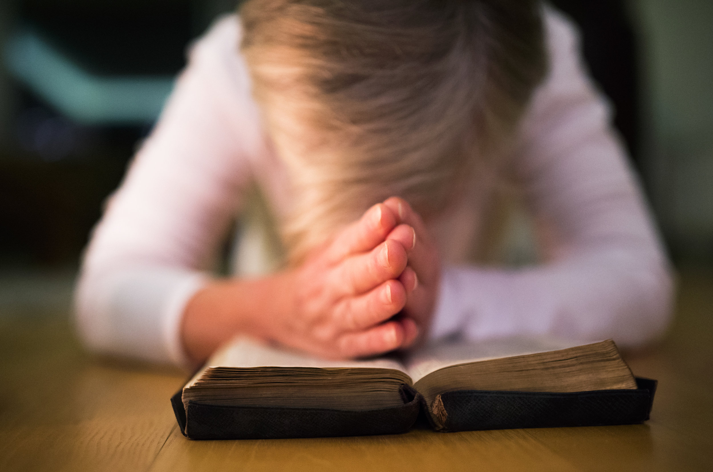 graphicstock-unrecognizable-woman-praying-with-hands-clasped-together-on-her-bible-close-up_BOghq3d8G-.jpg
