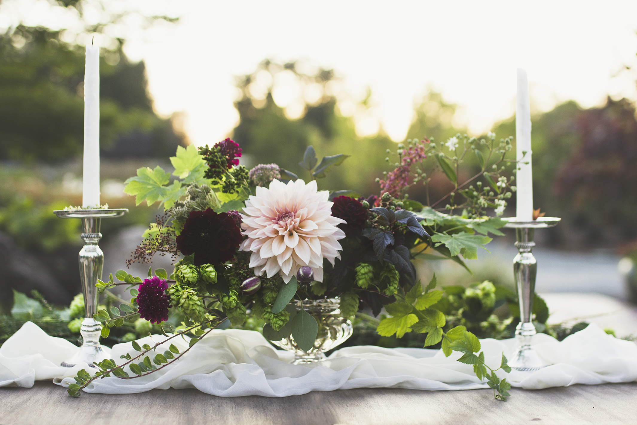 An Intimate sweetheart table set next to Pine Creek's waterfall at sunset