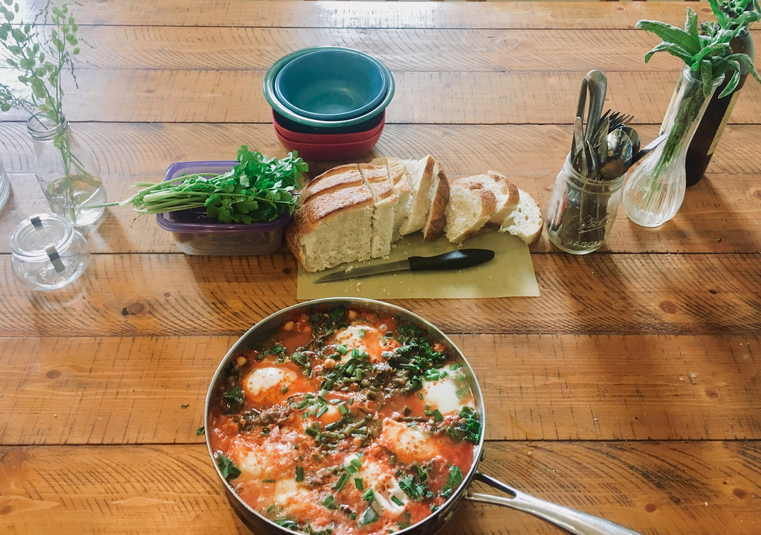 Farm lunch shakshuka served with cilantro and sourdough bread