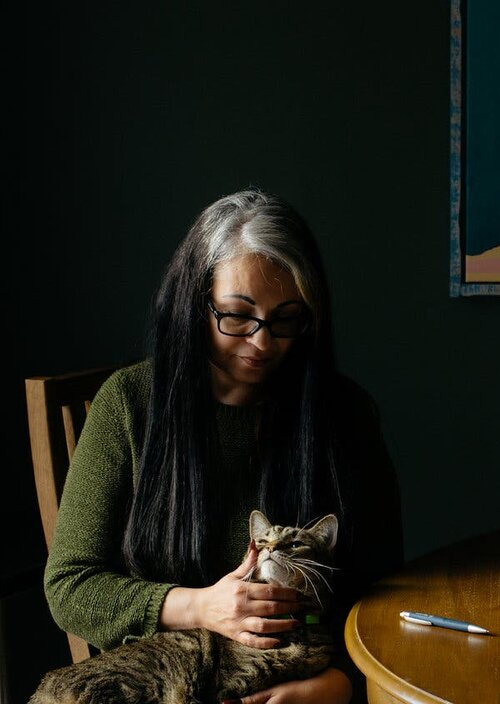Ana Helfer, at home with one of her cats, Marley, survived years of emotional and physical abuse from her husband  Credit Alex Flynn for The New York Times