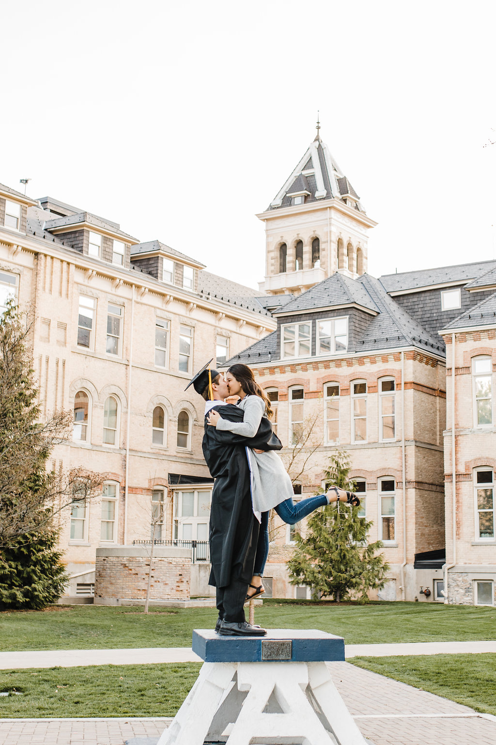 couples graduation hug utah state university logan utah cache valley on the A old main