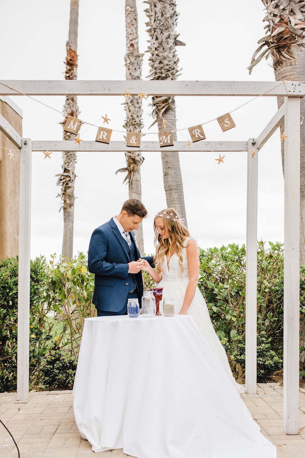 bride and groom under wedding arch los angeles california wedding ceremony