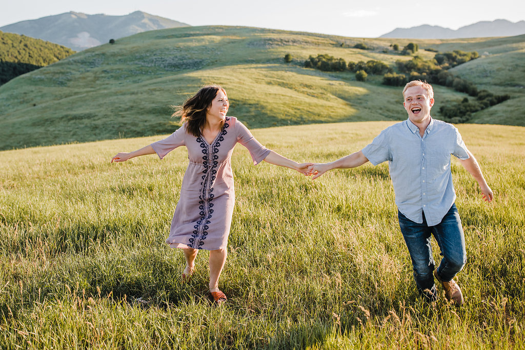 fun engagement photo couple running hills northern utah professional wedding photography calli richards adventurous engagement photos