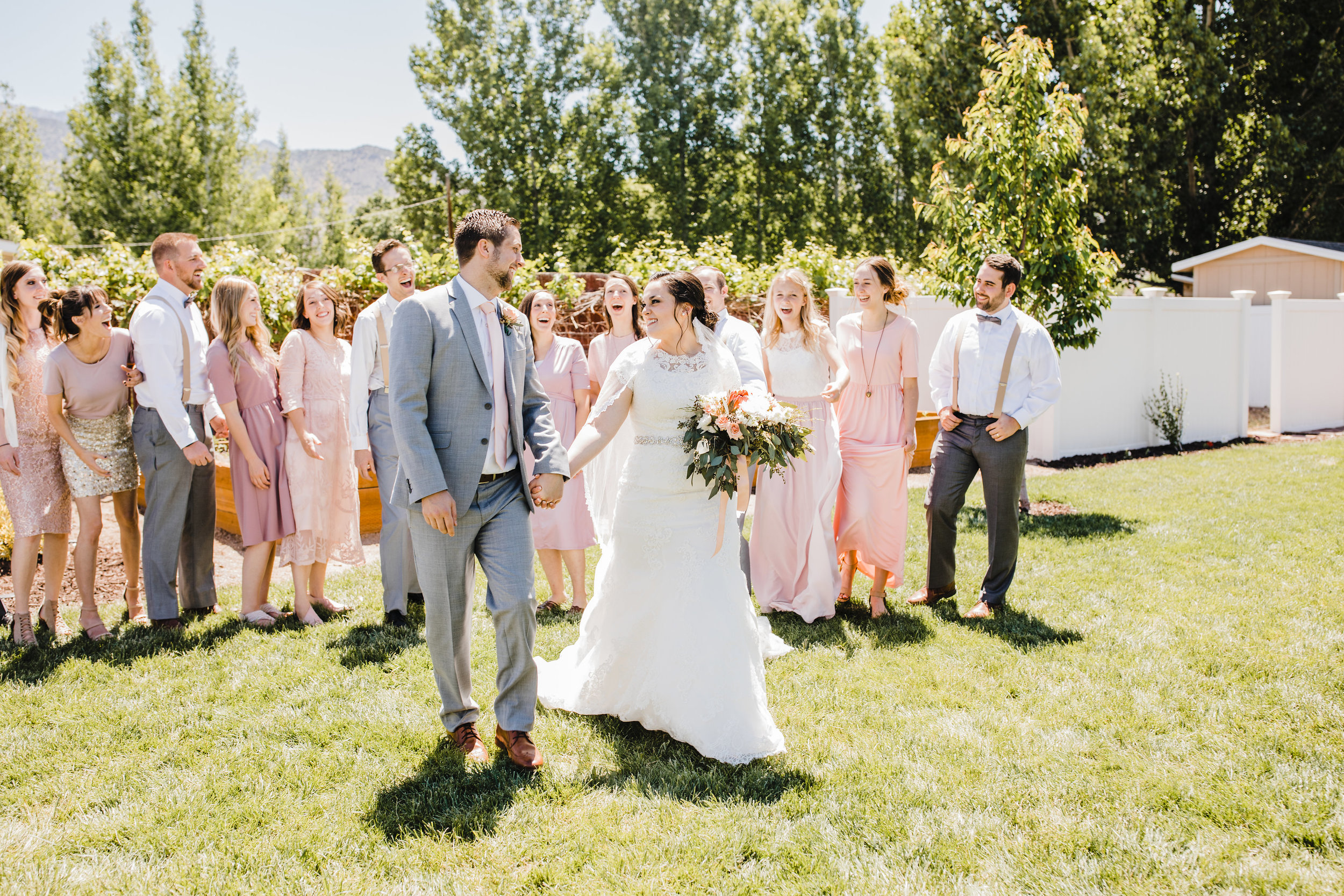 professional wedding photographer in provo utah utah valley wedding photographer lds backyard wedding laughter blush bridesmaids dresses holding hands groomsmen suspenders