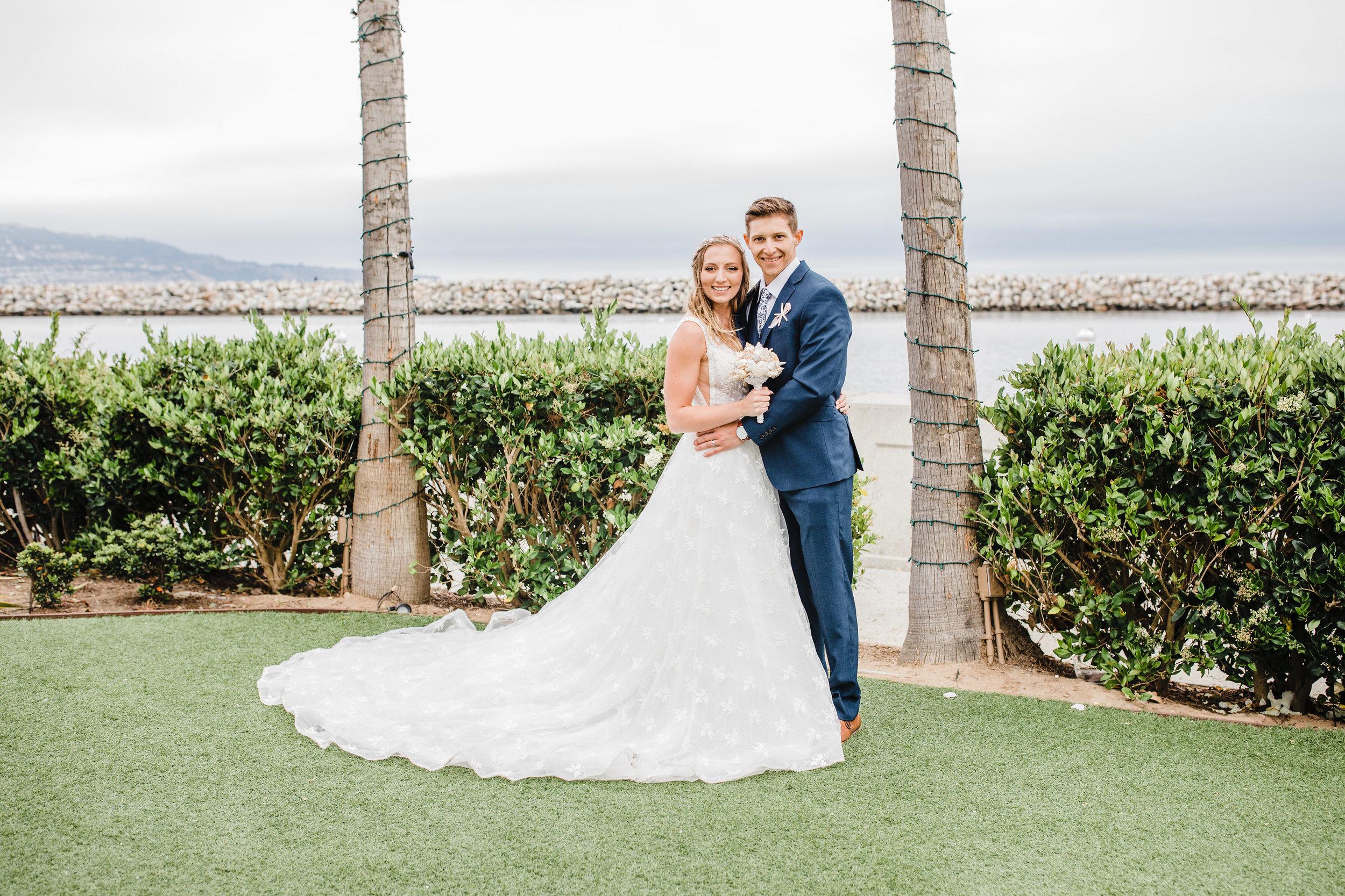 professional wedding photographer in park city utah wedding dress train bride and groom palm tree beach wedding smiling