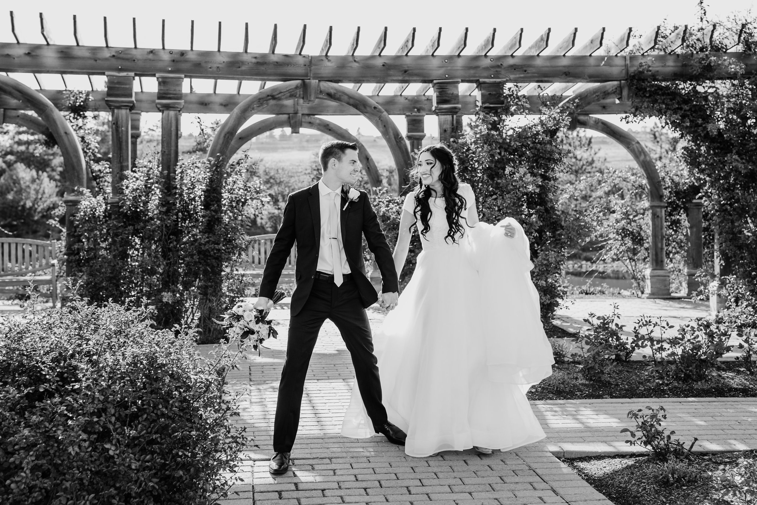 Professional Wedding photographer in cache valley utah holding hands outdoor garden summer wedding modest wedding dress