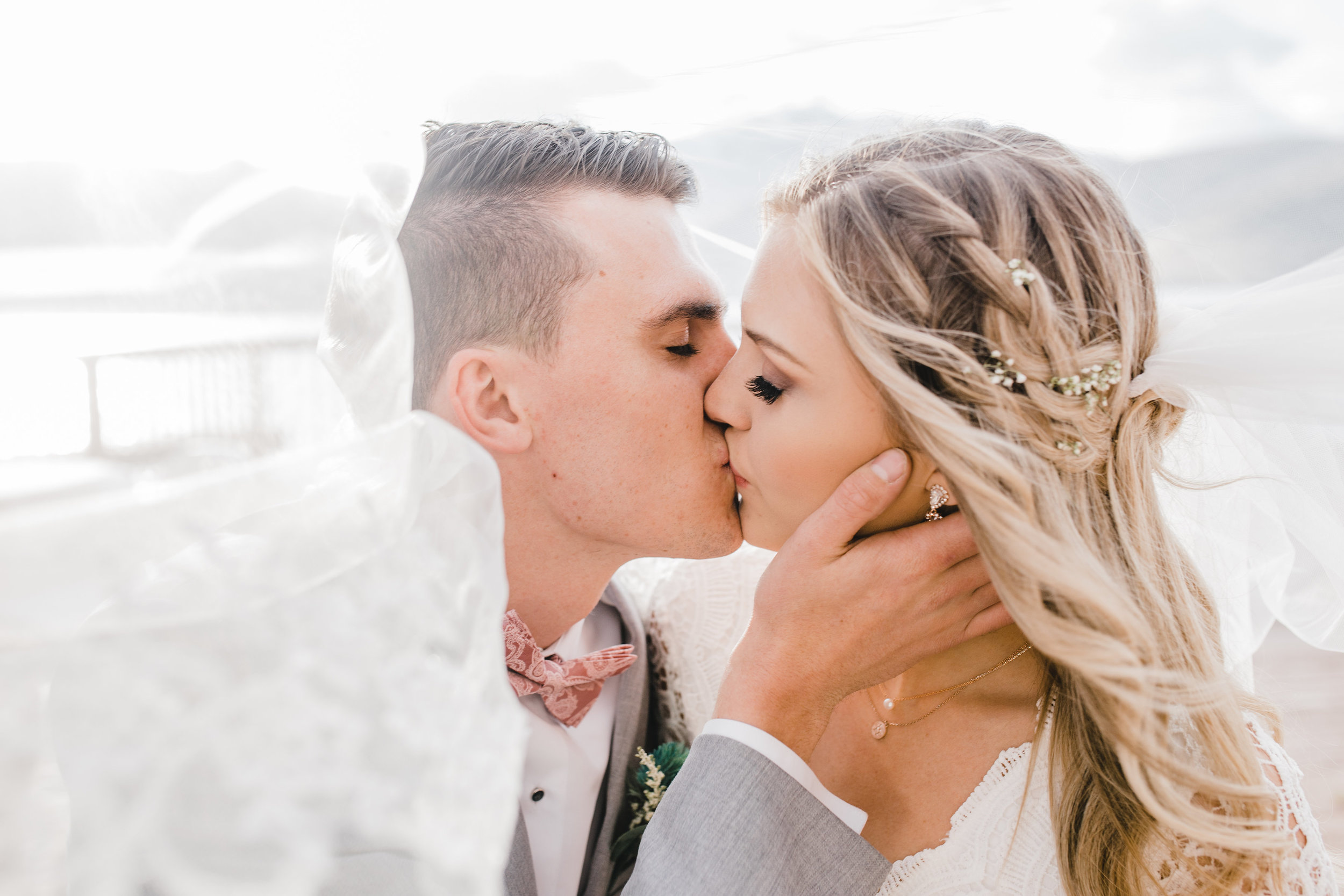 best wedding photographer in cache valley utah kissing blowing veil wedding bow tie