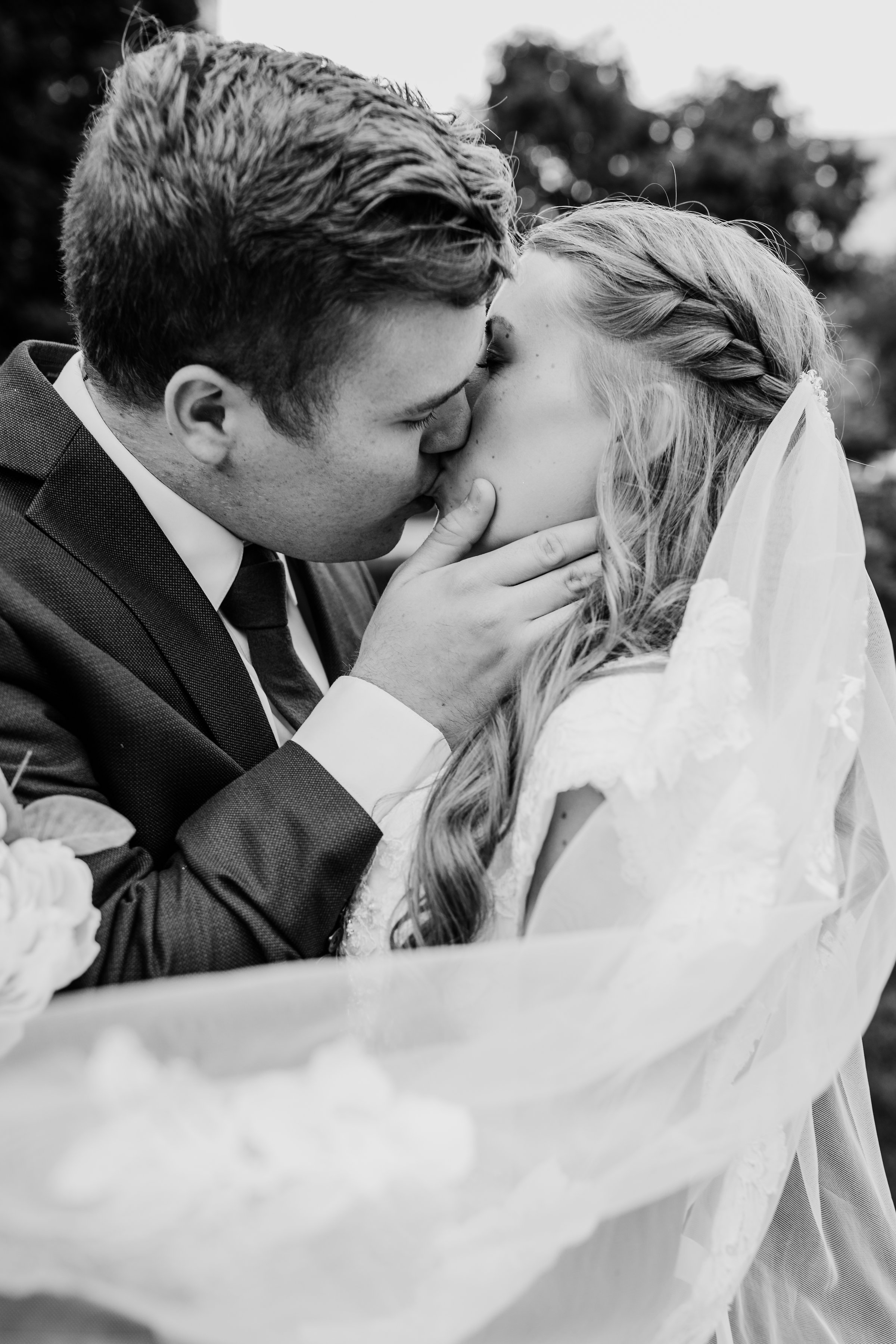 best wedding photographer in lakewood colorado kissing bride and groom billowy wedding veil lds