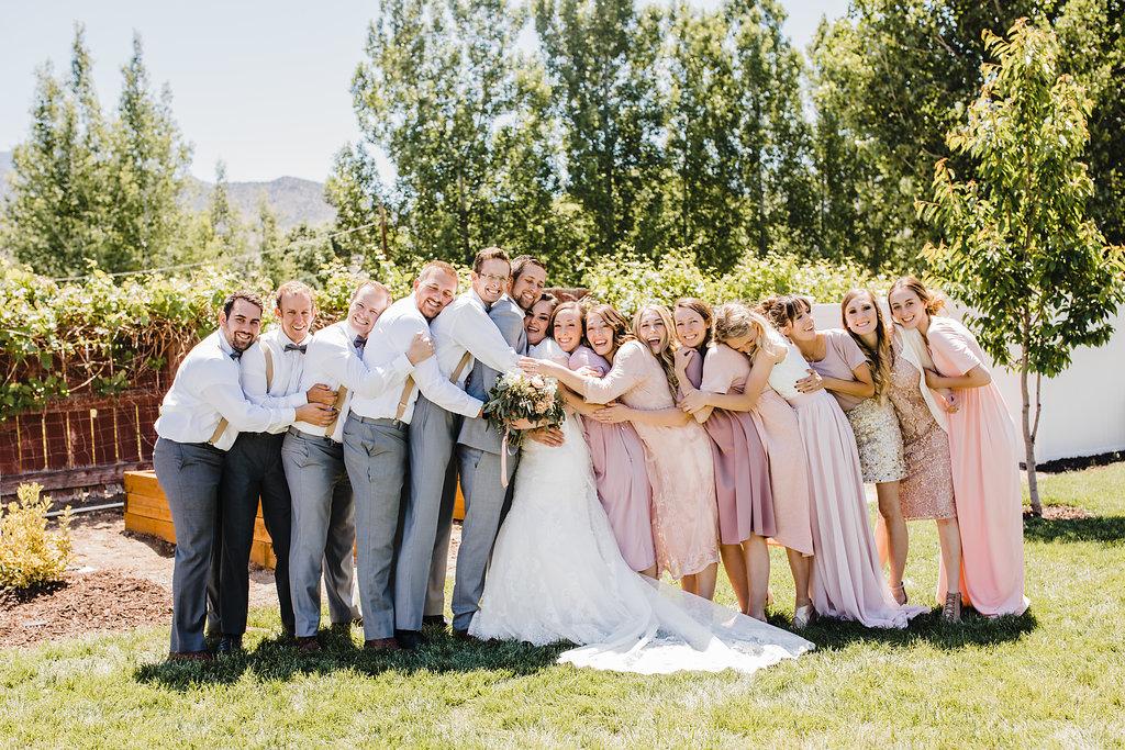 wedding party hug monroe utah groomsmen and bridesmaids hug bride and groom rose gold and suspenders