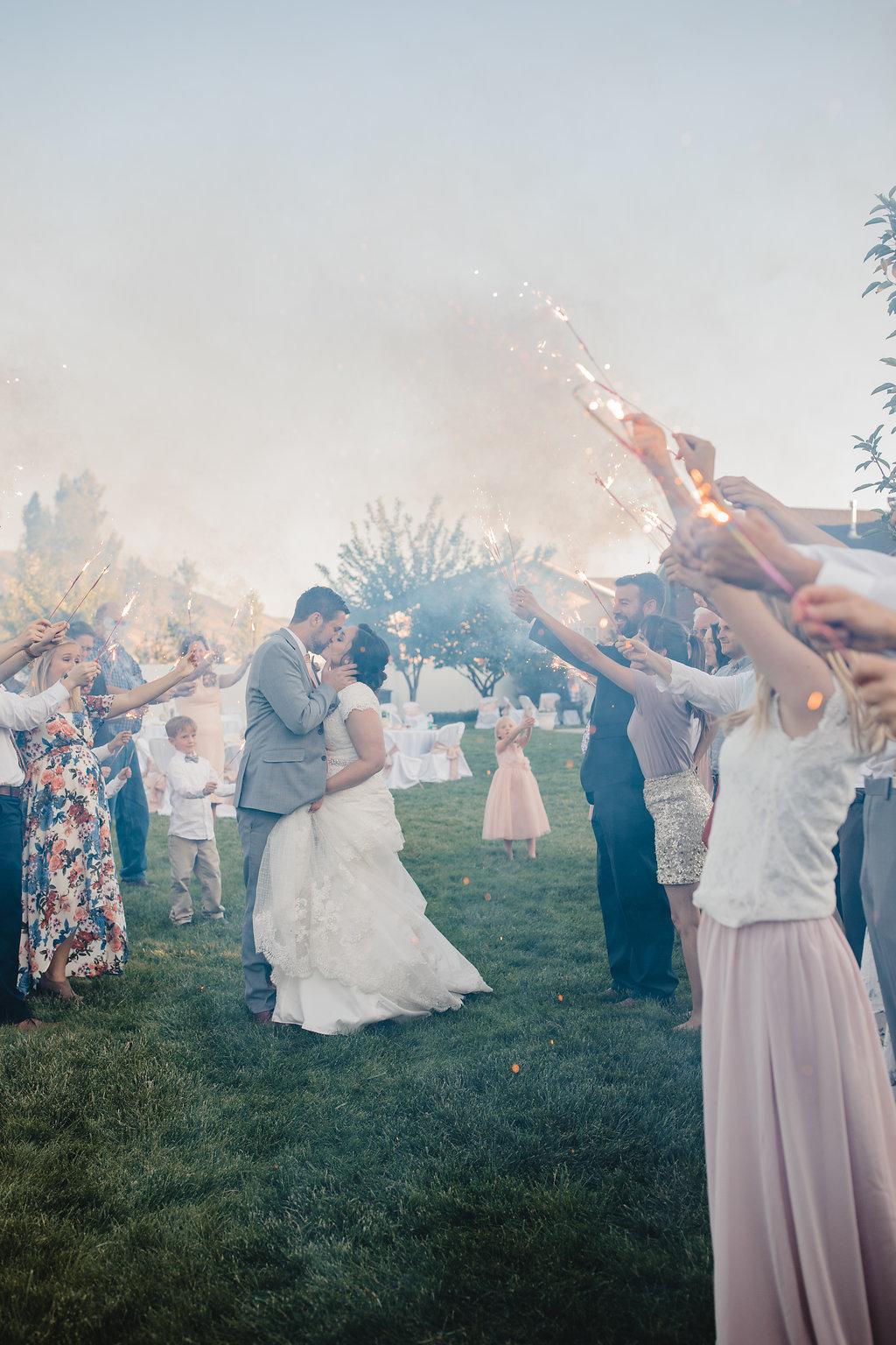 bride and groom send off with sparklers wedding day kiss monroe utah wedding photographer calli richards
