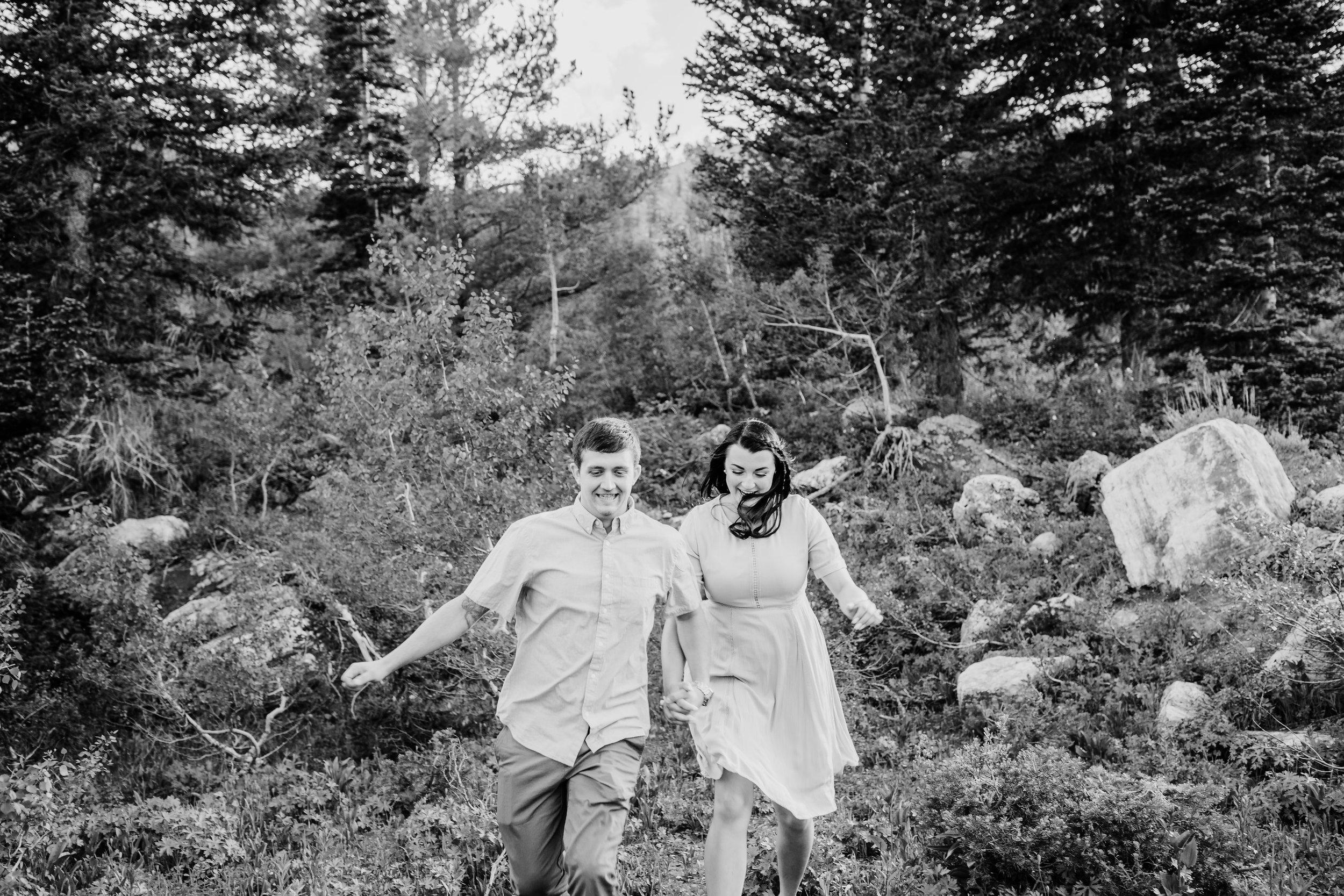 professional engagement photographer in logan utah running mountain engagement holding hands laughing