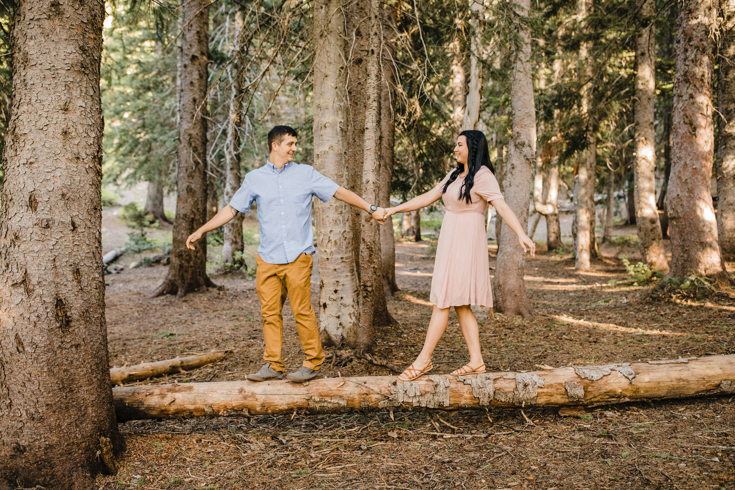 cache valley engagement photographer holding hands walking on log smiling forrest
