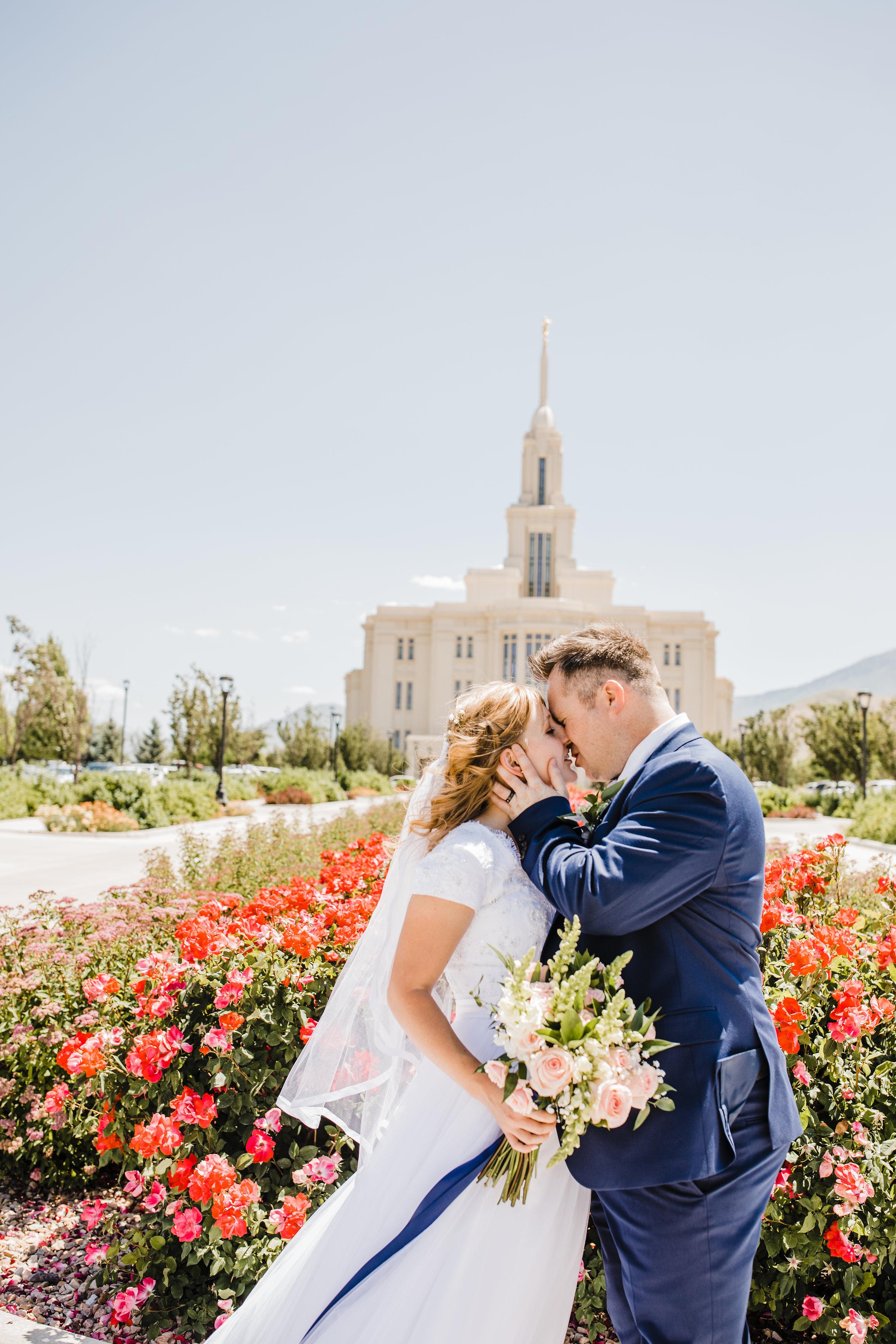 professional wedding photographer in logan utah lds temple wedding kissing red flowers