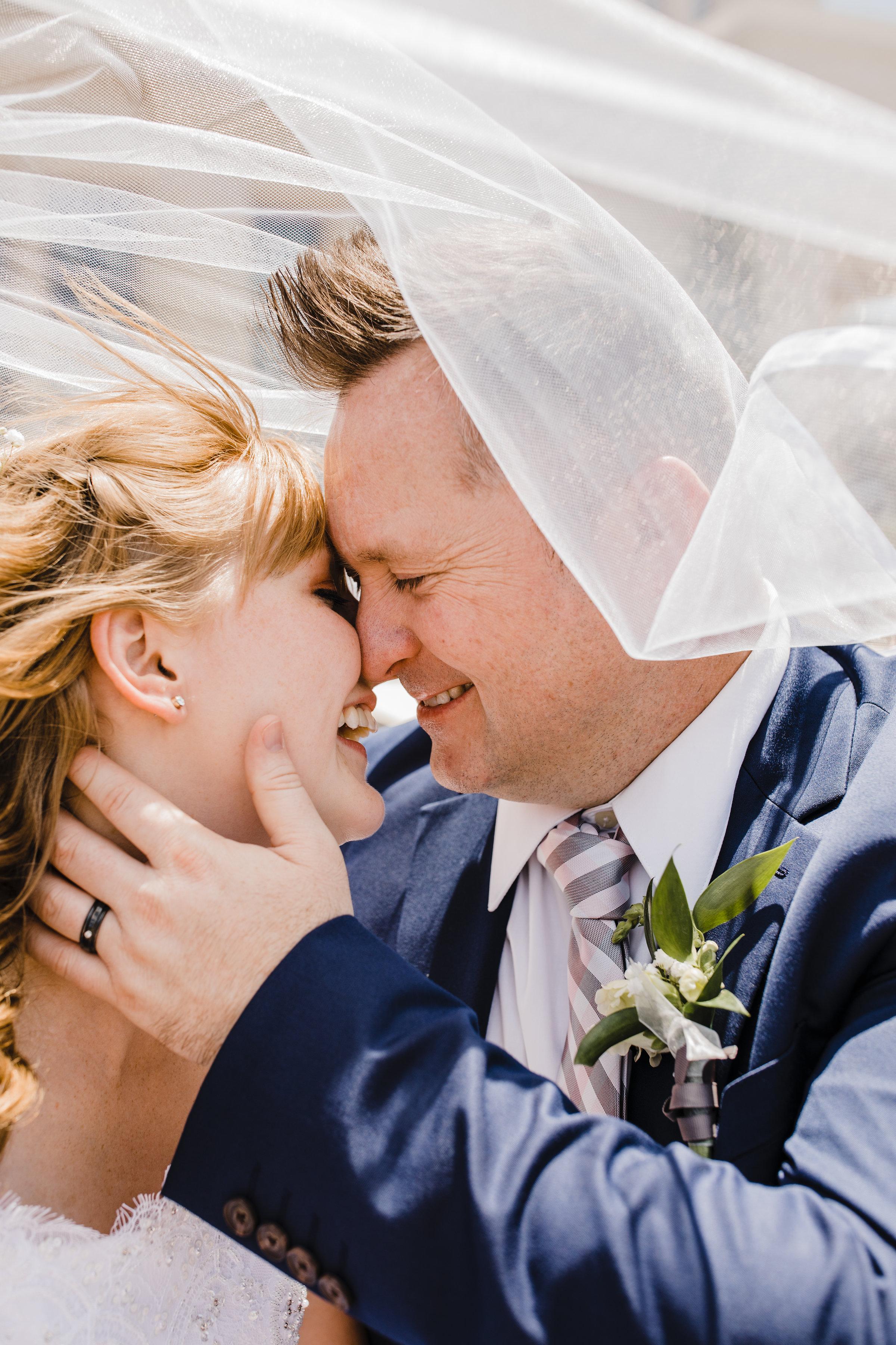 wedding photographer in logan utah flying veil kissing smiling romantic