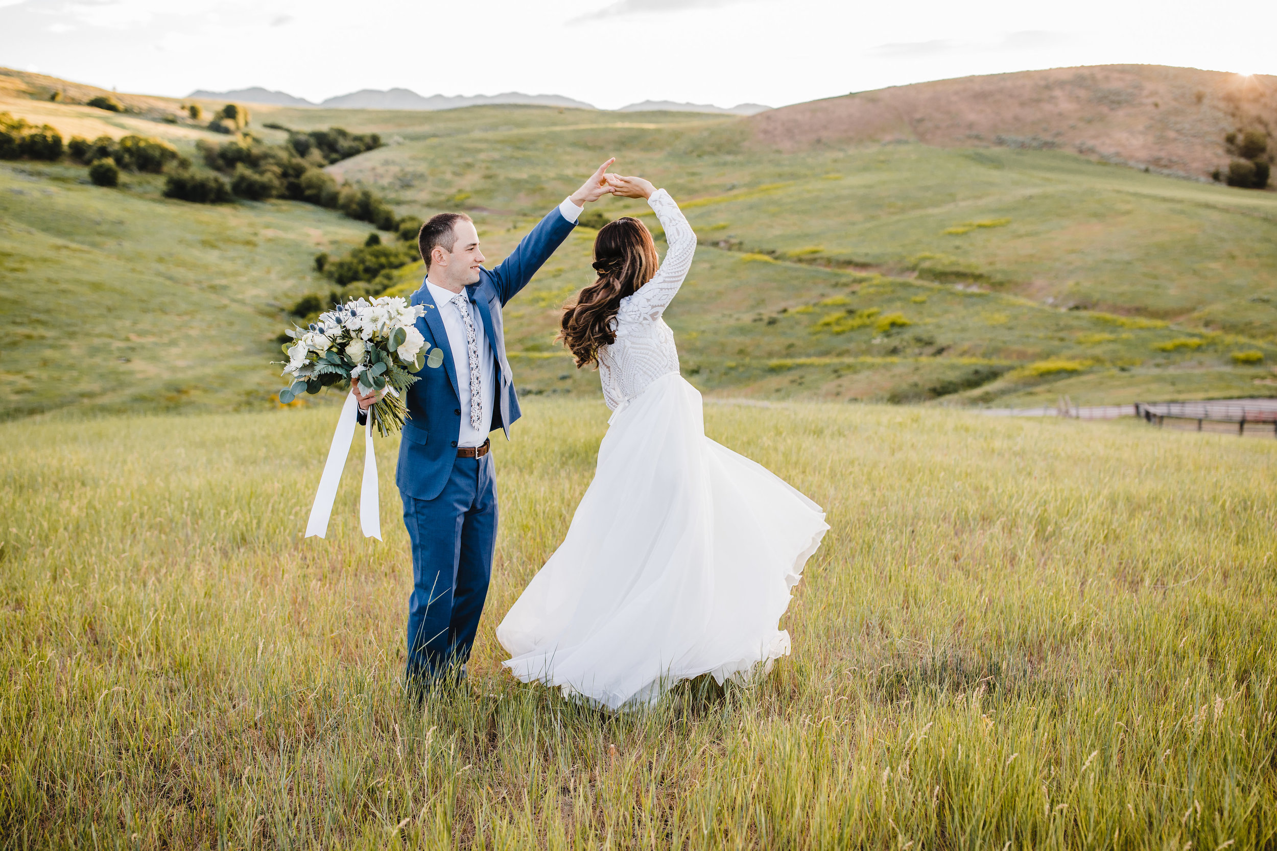wedding photographer in logan utah spinning long veil field mountains