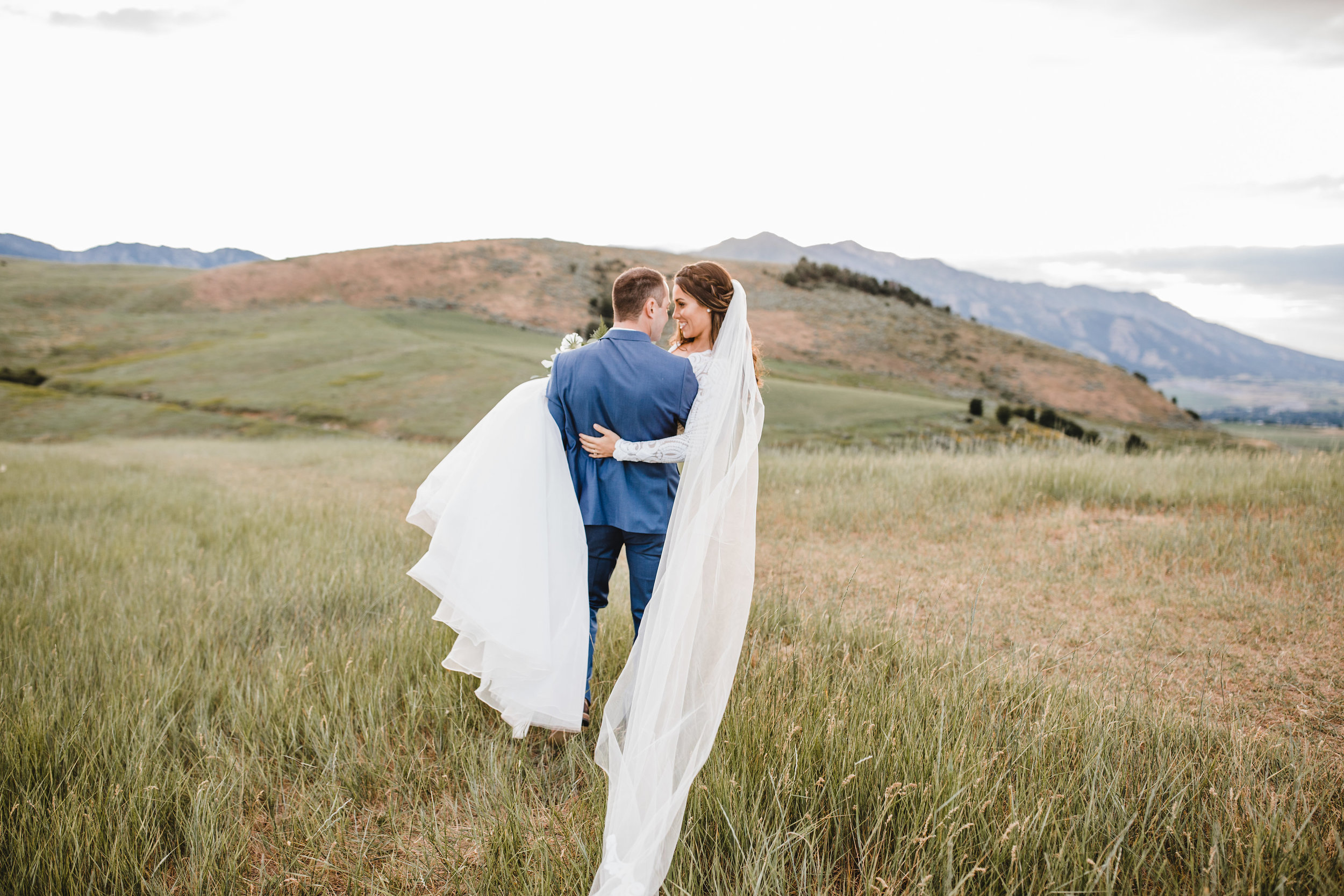 best photographer in logan utah veil kissing carrying field