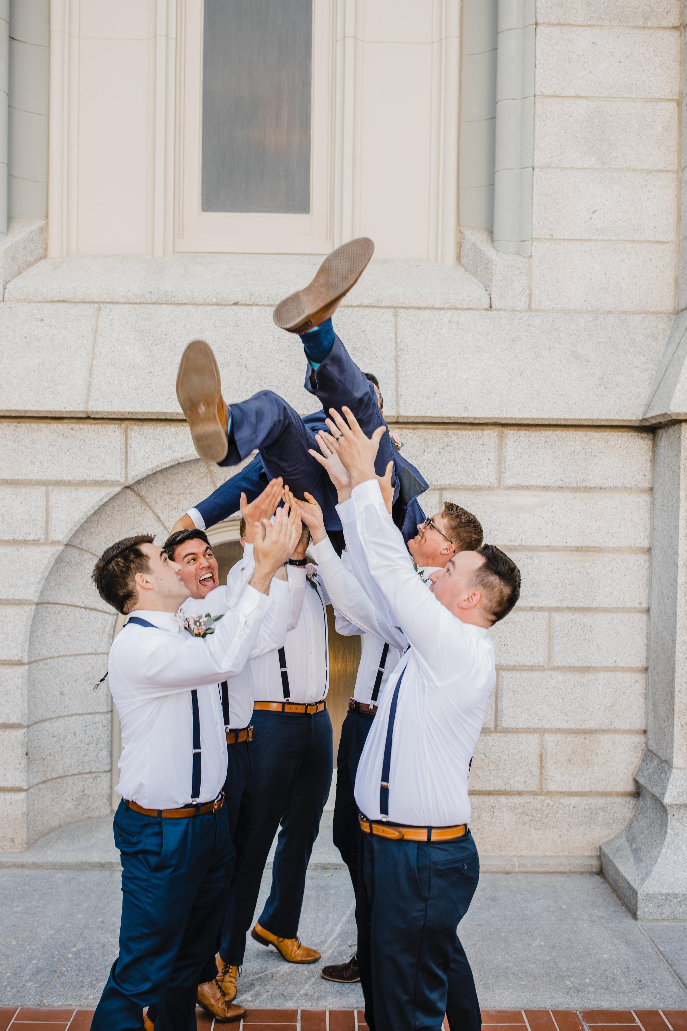 professional salt lake city photographer groomsmen lds temple crowd surfing
