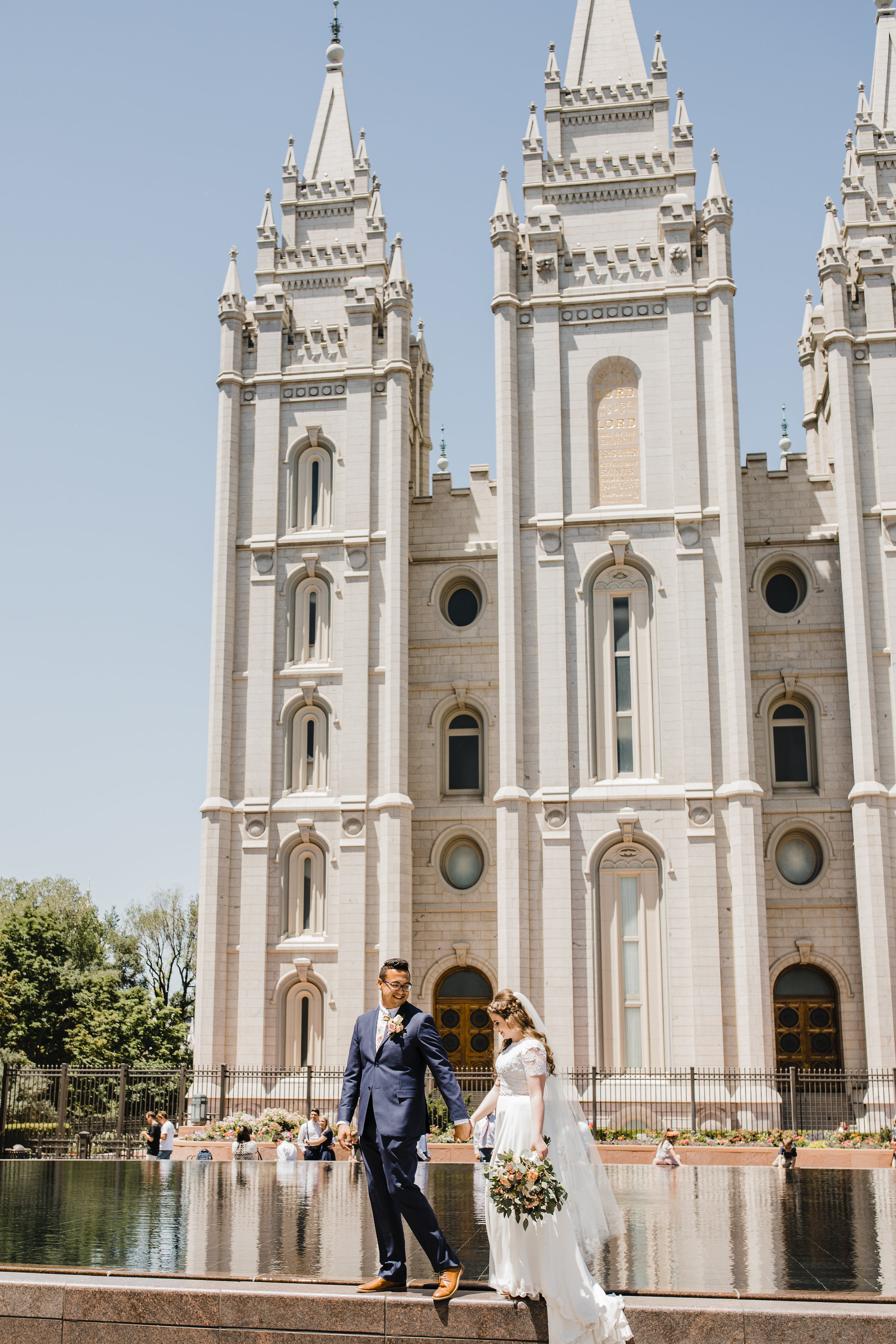 salt lake city wedding photographer walking water lds temple grounds holding hands