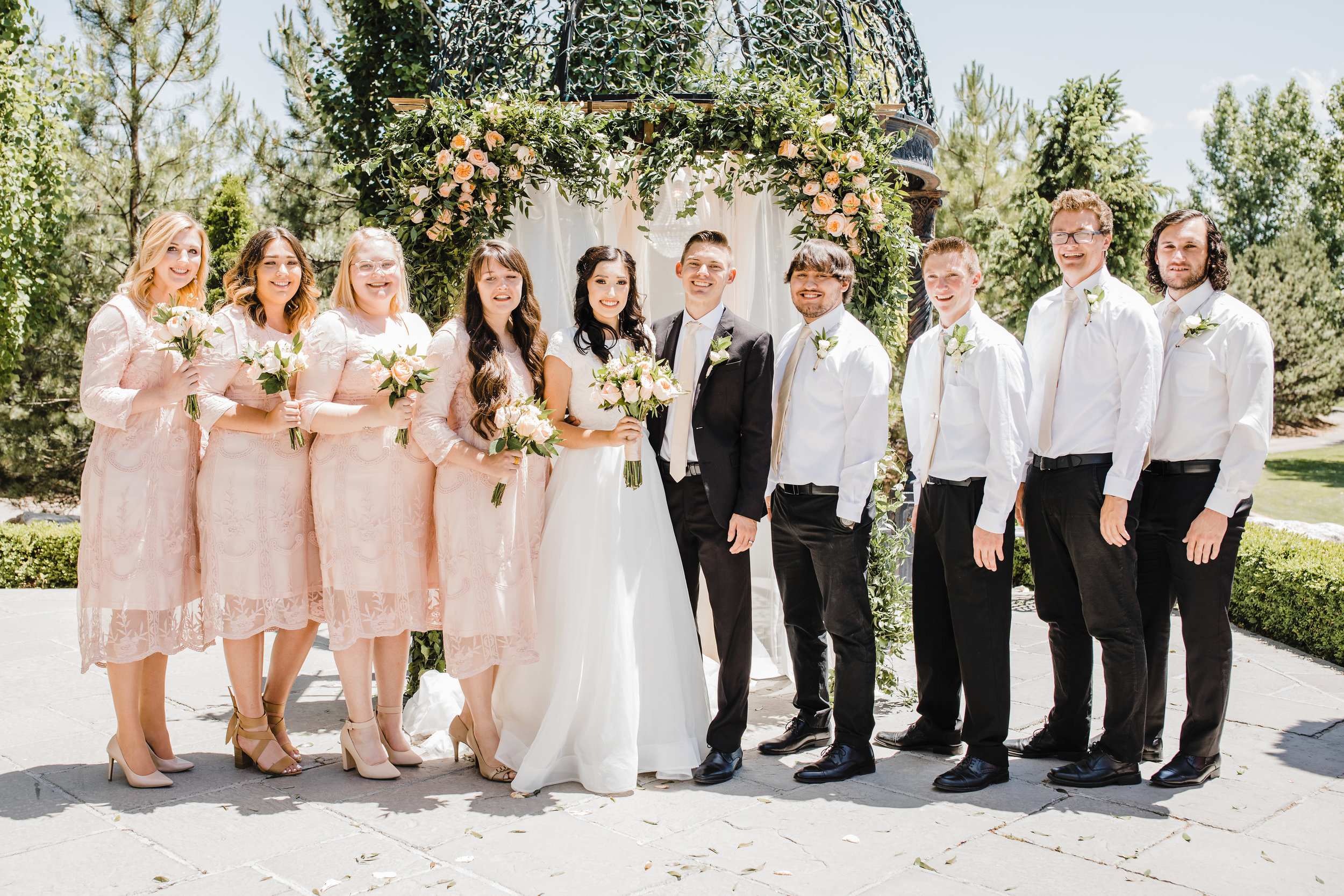 wedding party in front of wedding arch blush roses bridesmaids and groomsmen orem utah wedding day photography