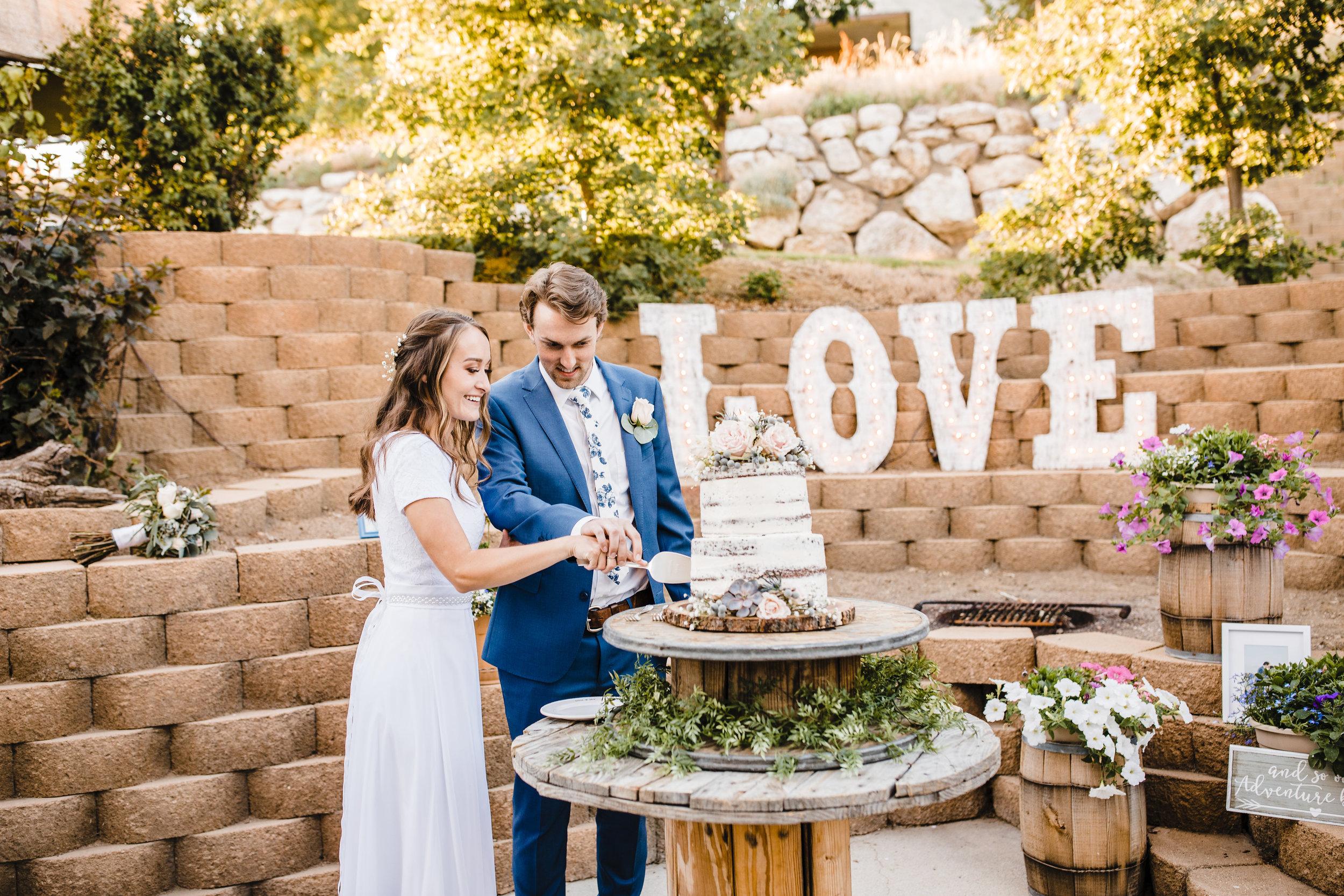 logan utah wedding photographer outdoor reception cake cutting love sign