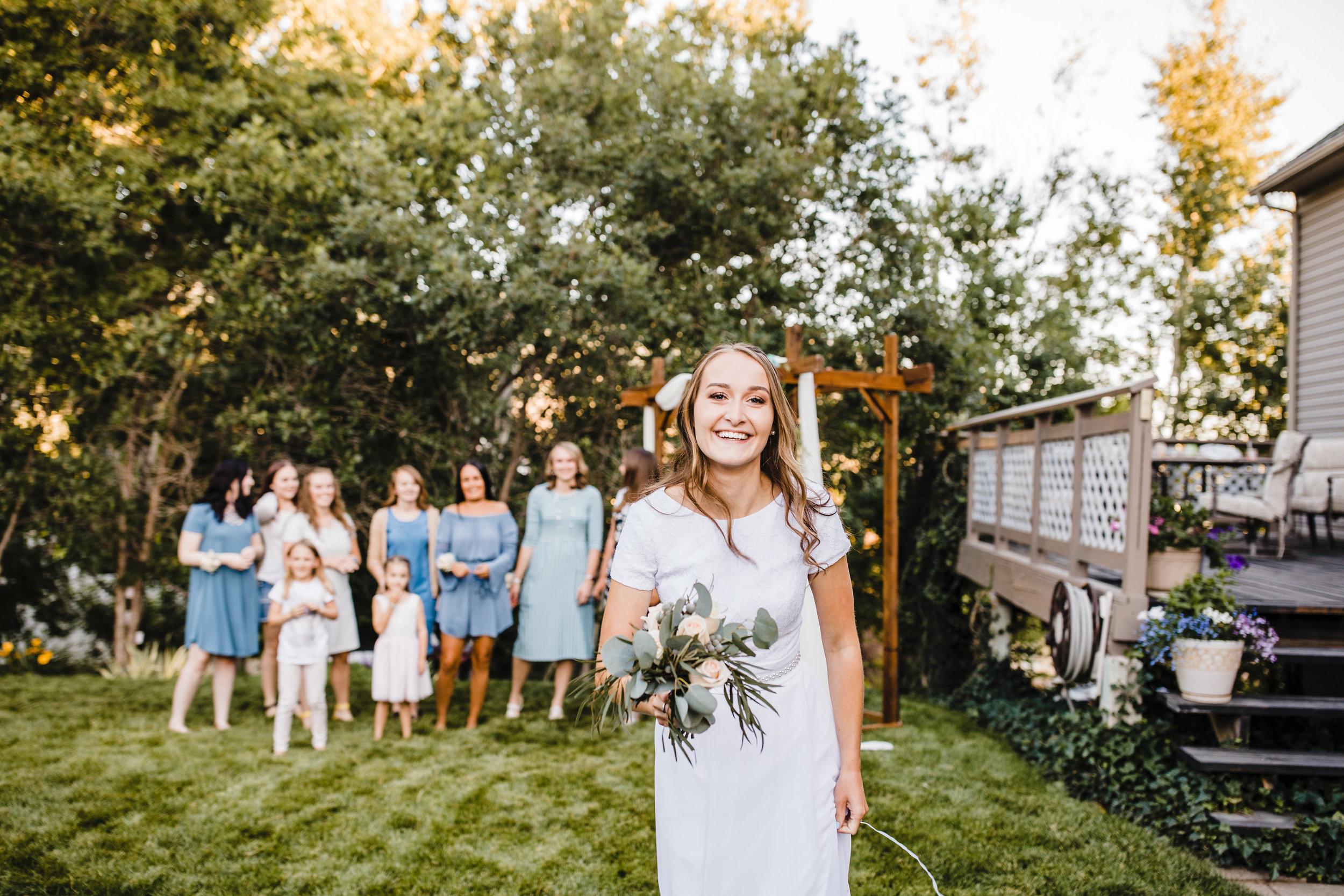 cache valley wedding photographer outdoor wedding reception bouquet toss blue bridesmaids