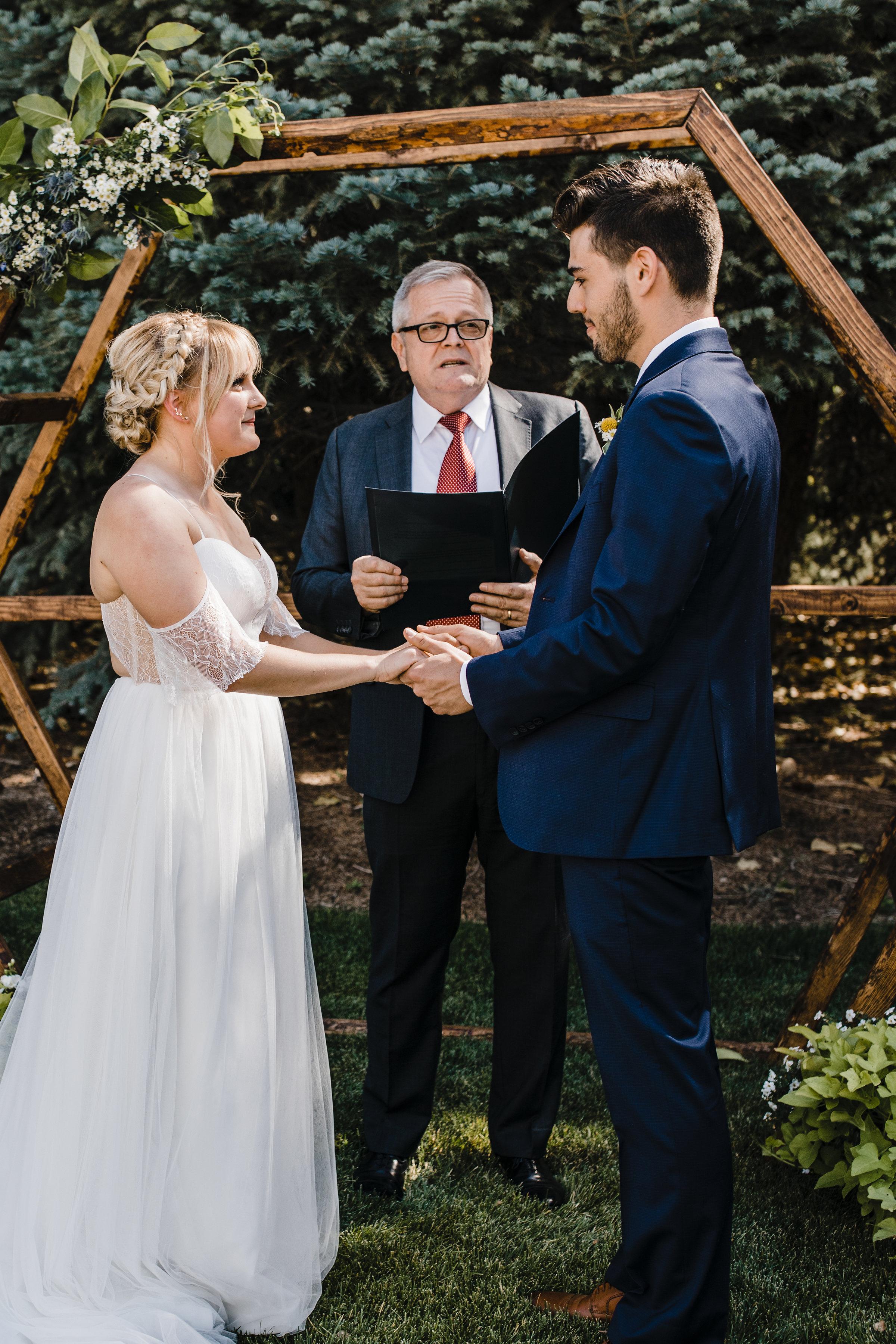 Salt Lake City Utah Professional Photographer bohemian outdoor wedding geometric wedding arch vows holding hands braids