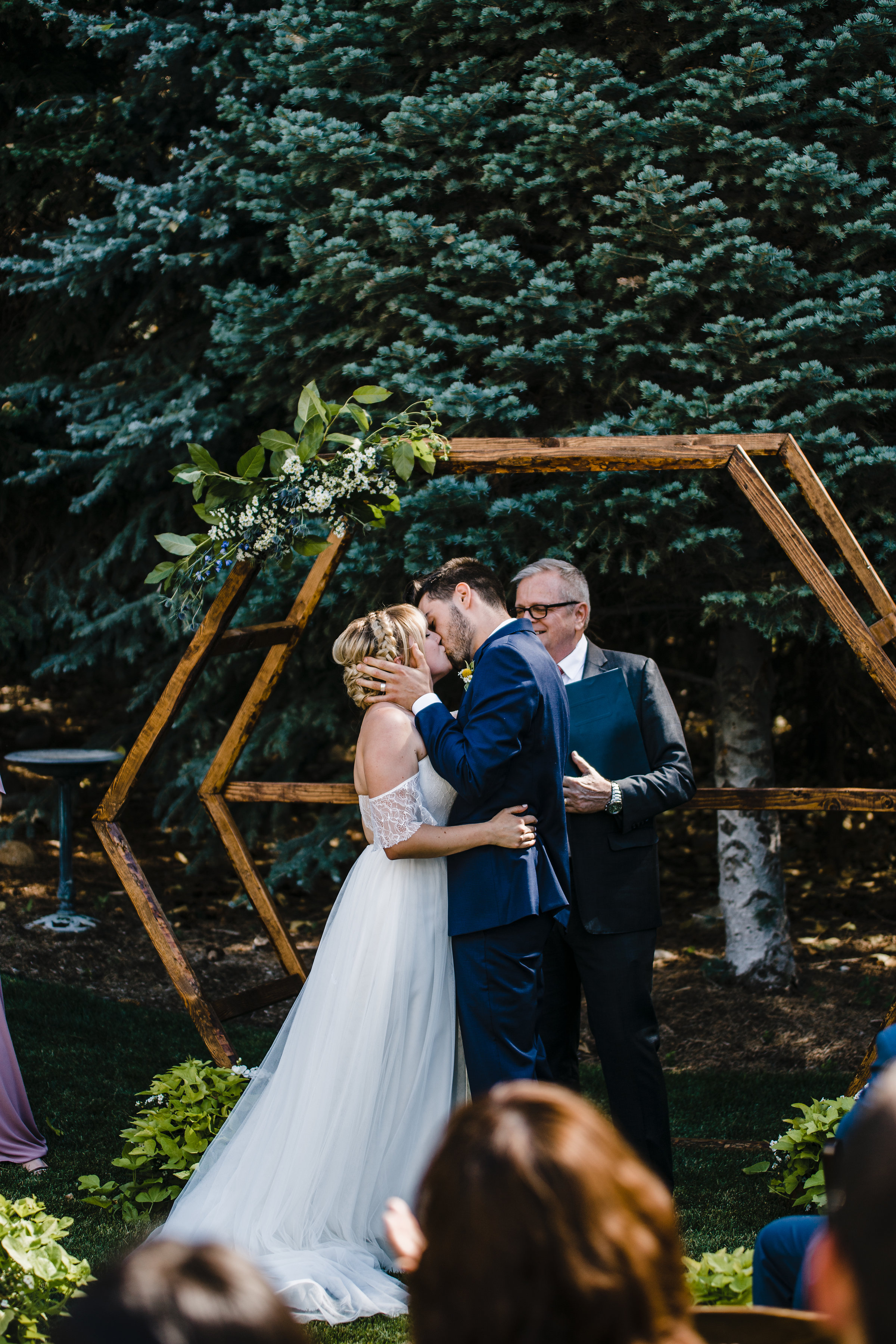 Salt Lake City utah wedding photographer wedding exit outdoor ceremony bohemian wedding arch florals geometric kissing