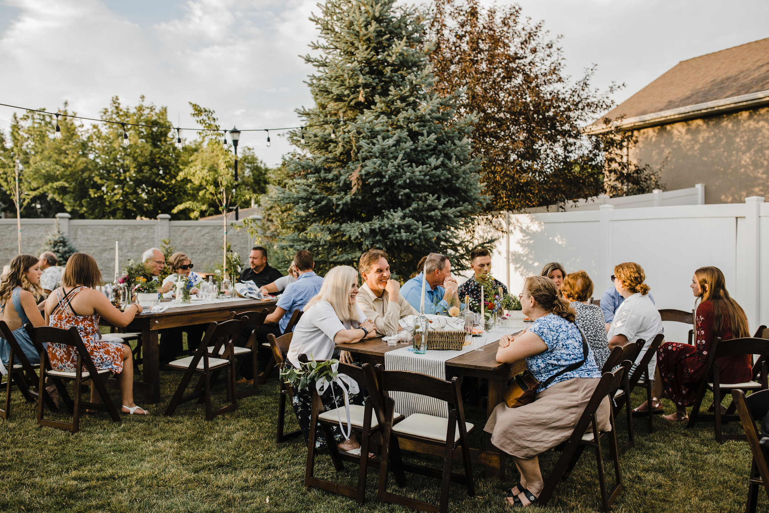 South Jordan Utah professional wedding photographer wedding guests cache valley photographer outdoor wedding tables wooden chairs string lights